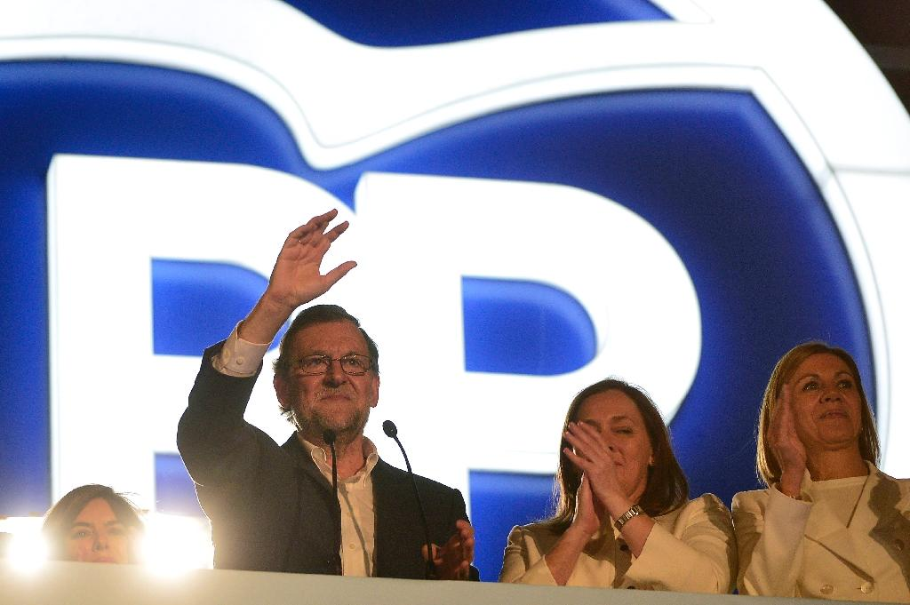 Spanish Prime Minister and Popular Party (PP) leader Mariano Rajoy waves alongside his wife Elvira Fernandez (2ndR) at the PP's headquarters after the results of Spain's general election in Madrid on December 20, 2015 (AFP Photo/Jose Jordan)