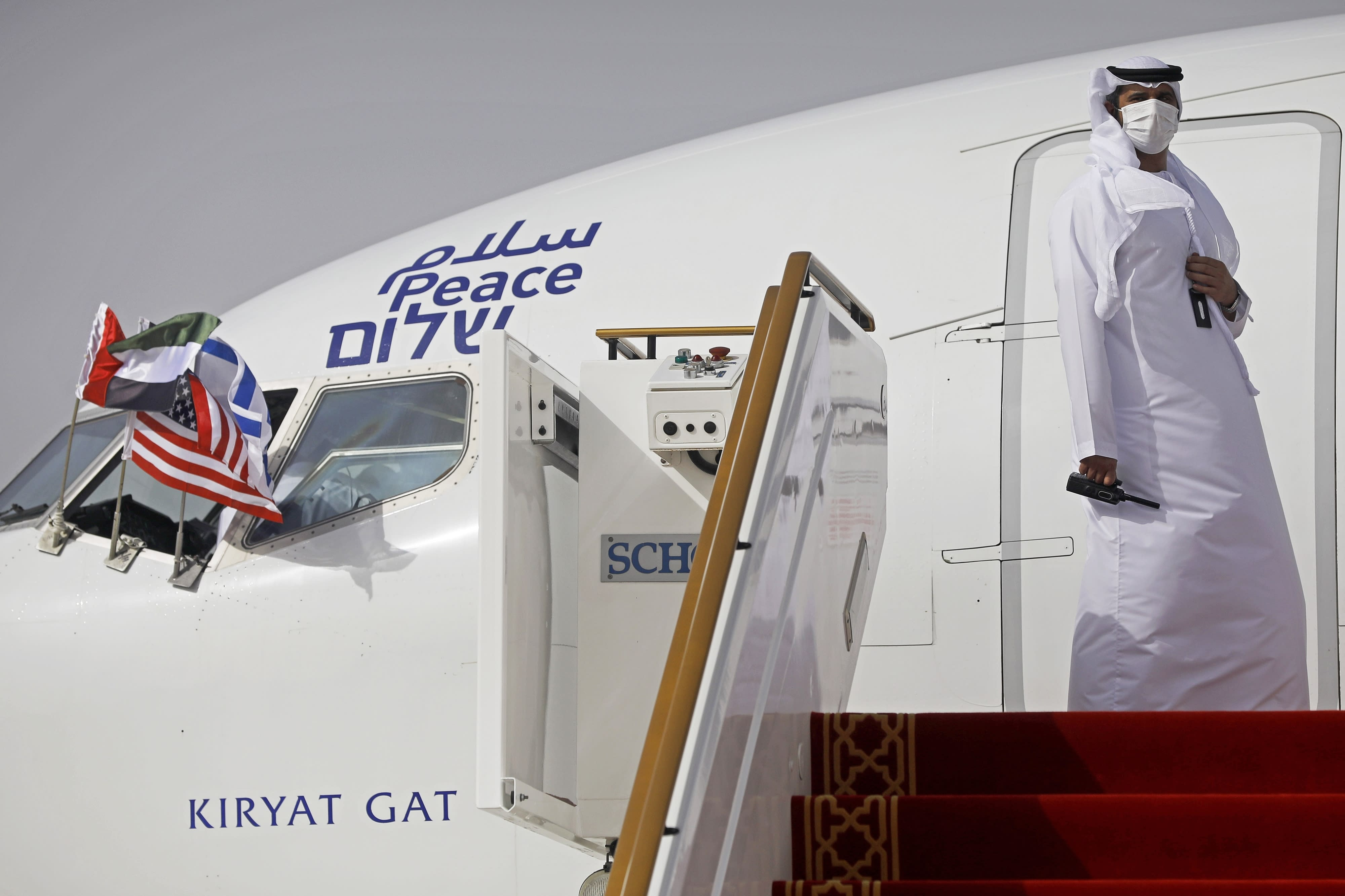 """FILE - In this Monday, Aug. 31, 2020 file photo, an official stands at the door of an Israeli El Al airliner after it landed in Abu Dhabi, United Arab Emirates. The Saudi Press Agency announced Wednesday, Sept. 2, 2020, that it will allow flights """"from all countries"""" to cross its skies to reach the United Arab Emirates. The announcement comes just days after Saudi Arabia allowed the first direct Israeli commercial passenger flight to use its airspace to reach the UAE, signaling acquiescence for a breakthrough U.S.-brokered deal by the United Arab Emirates to normalize relations with Israel. (Nir Elias/Pool Photo via AP, File)"""