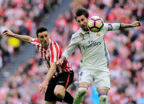 El delantero español Aritz Aduriz (I) del Athletic de Bilbao lucha por la pelota con el defensa  Sergio Ramos, de Real Madrid, en partido de la Liga española jugado el 18 de marzo de 2017 en estadio  San Mamés, en Bilbao