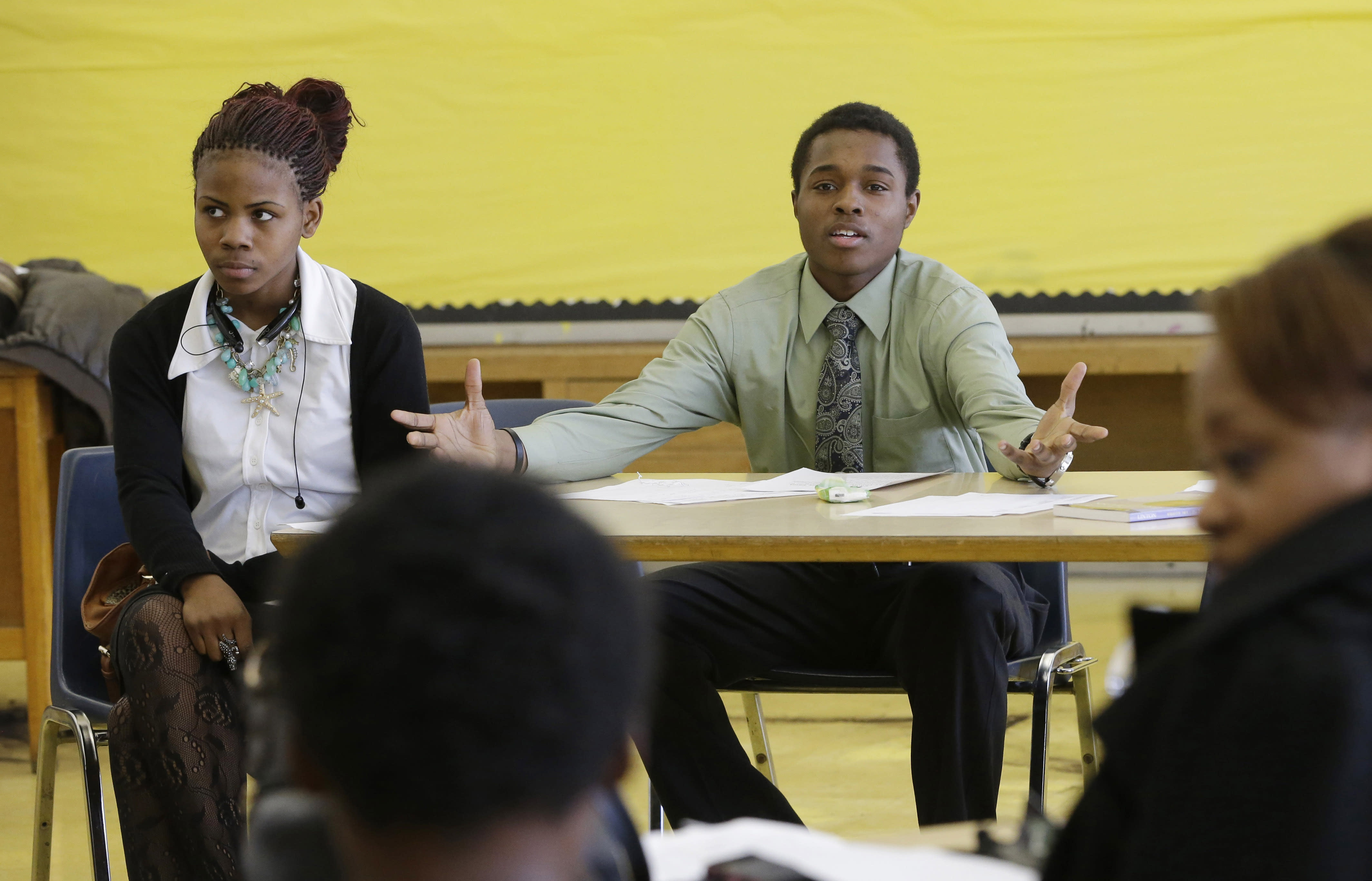 "In this Feb. 27, 2014 photo, student Jalen Pickett, talks during a class that teaches anger management and conflict resolution skills at Cody High School in Detroit. Jalen, now a diligent student with aspirations to be a defense lawyer, had an inauspicious start to high school. His fighting earned him a spot in the new police department program - the Children in Trauma Intervention Camp which gives students an alternative to expulsion in the form of training and counseling from police officers and other adult mentors. ""If Detroit can change, it's up to the youth to do it,"" Jalen says. ""I feel Detroit can come back. And if I do go away to college, I plan on coming back here and giving back to Detroit."" (AP Photo/Carlos Osorio)"