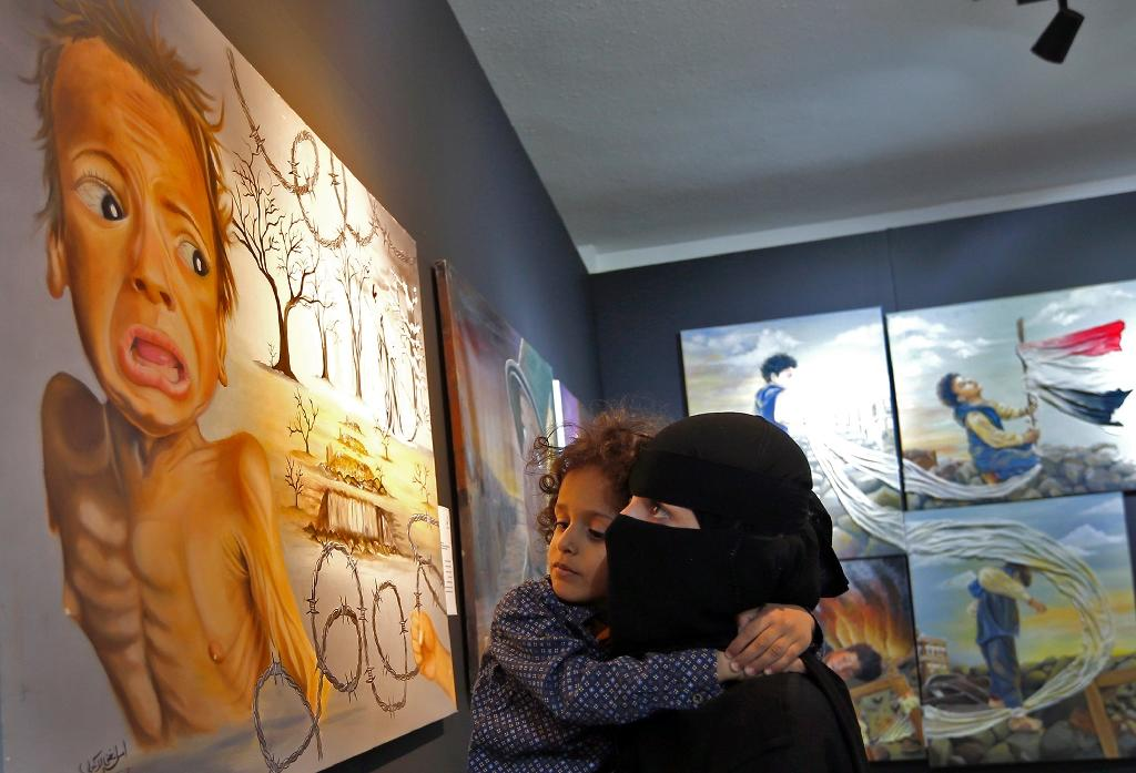 A Yemeni woman and her child visit an art exhibition in the rebel-held capital Sanaa on October 1, 2018 (AFP Photo/Mohammed HUWAIS)