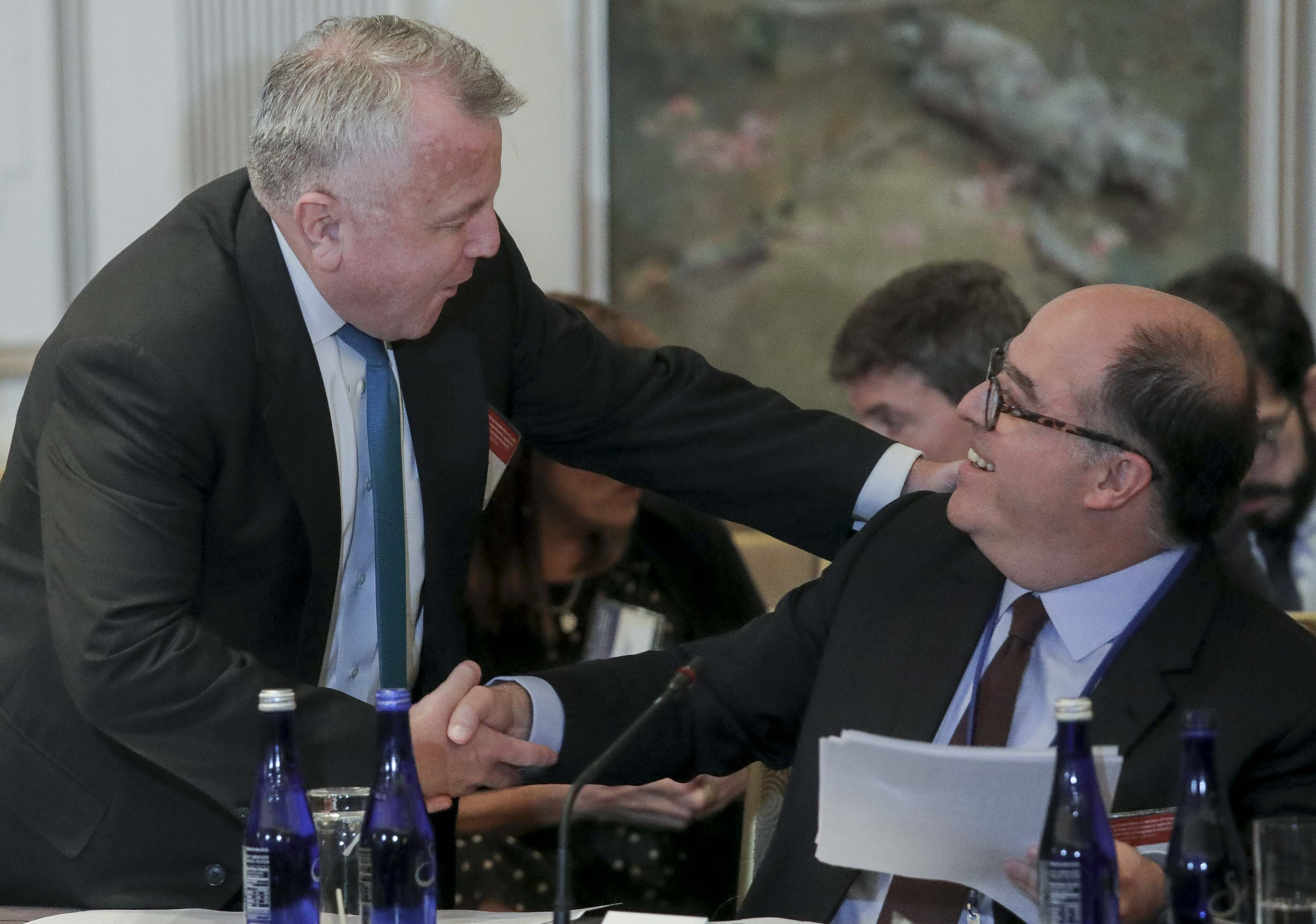 U.S. Deputy Secretary of State John Sullivan, left, and Julio Borges, an opposition leader in Venezuela, shake hands before a meeting organized by the OAS, to discuss sanctions on Venezuela, Monday Sept. 23, 2019, in New York. (AP Photo/Bebeto Matthews)