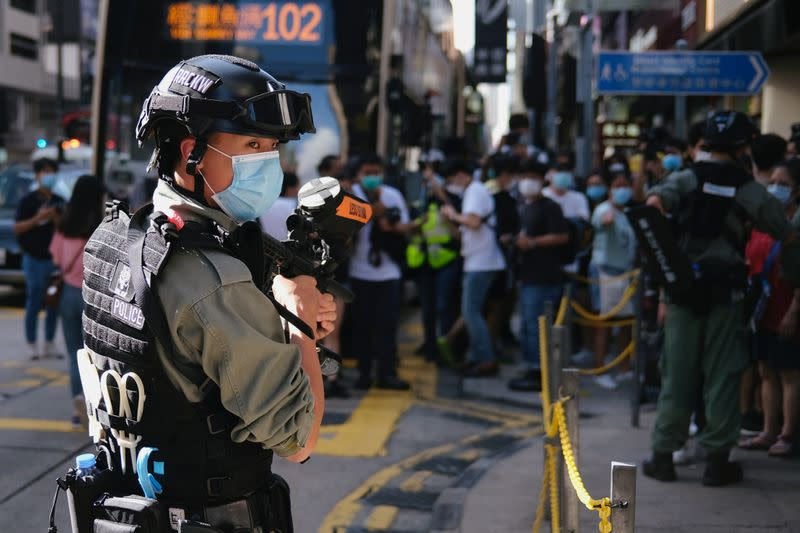 A riot police officer holds a pepper-spray projectile as he stands guard to avoid mass gathering during a protest against the looming national security legislation in Hong Kong