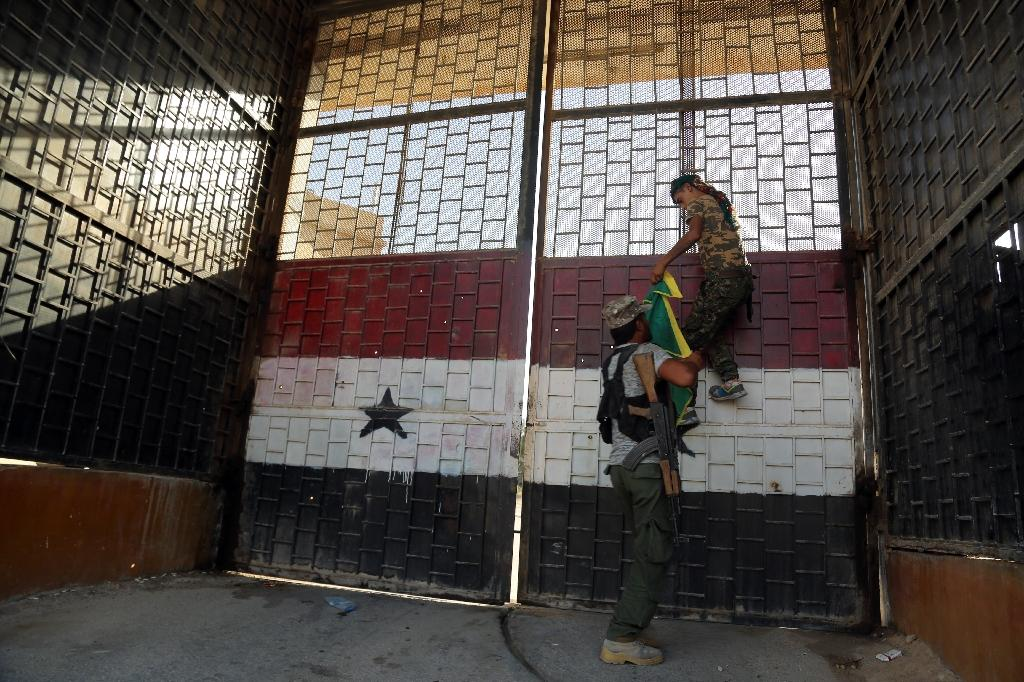 Kurdish fighters belonging to the People's Protection Units (YPG) put a YPG flag on the door of the central prison in the northeastern Syrian city of Hasakeh on August 23, 2016 (AFP Photo/Delil Souleiman)