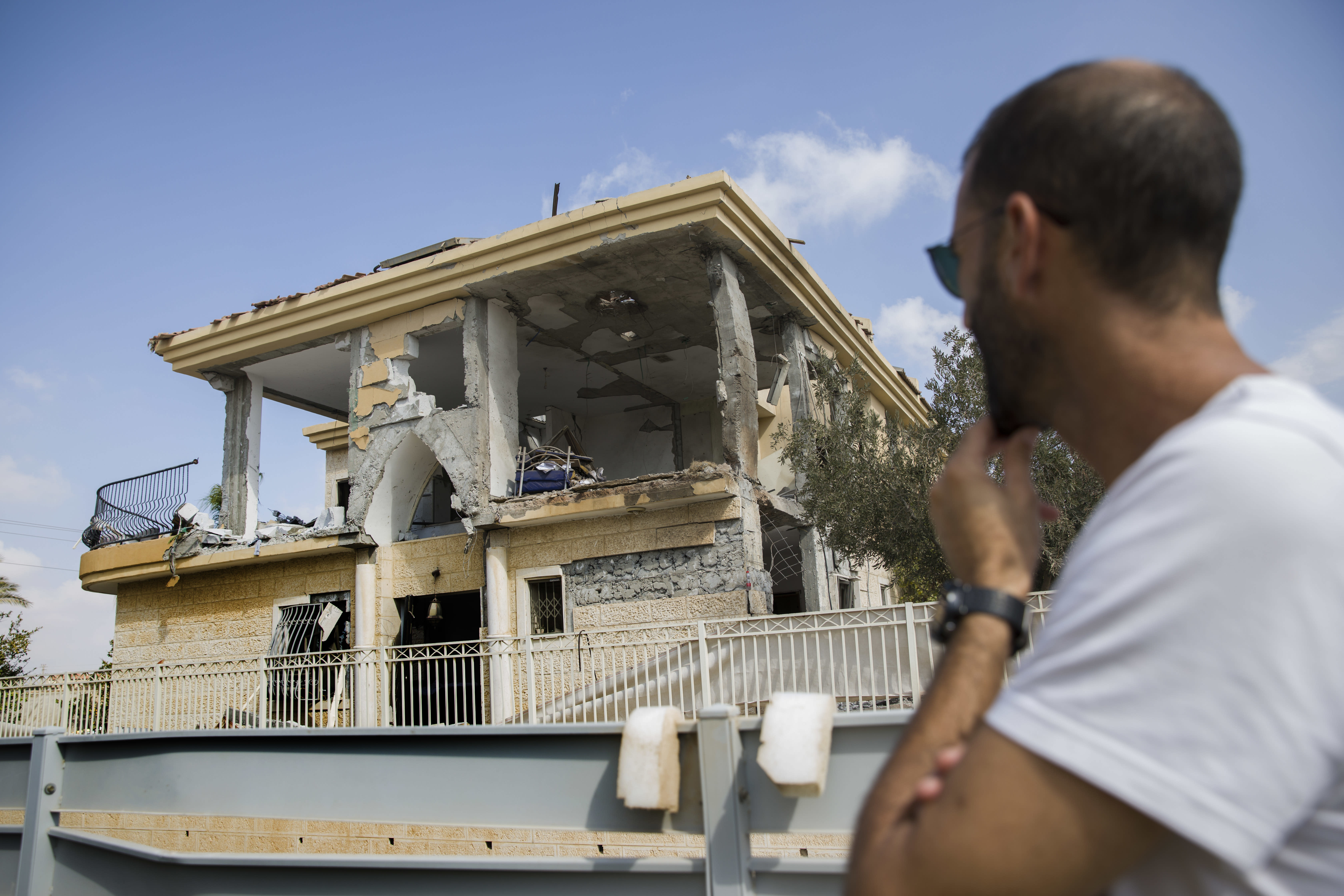 A man watches a house that was hit by a missile fired from Gaza Strip, in the city of Beersheba, southern Israel, Wednesday, Oct. 17, 2018. A medical service said a woman and her three children, whose home was struck, were being treated for shock after they fled to their shelter upon being awoken by warning sirens. (AP Photo/Tsafrir Abayov)
