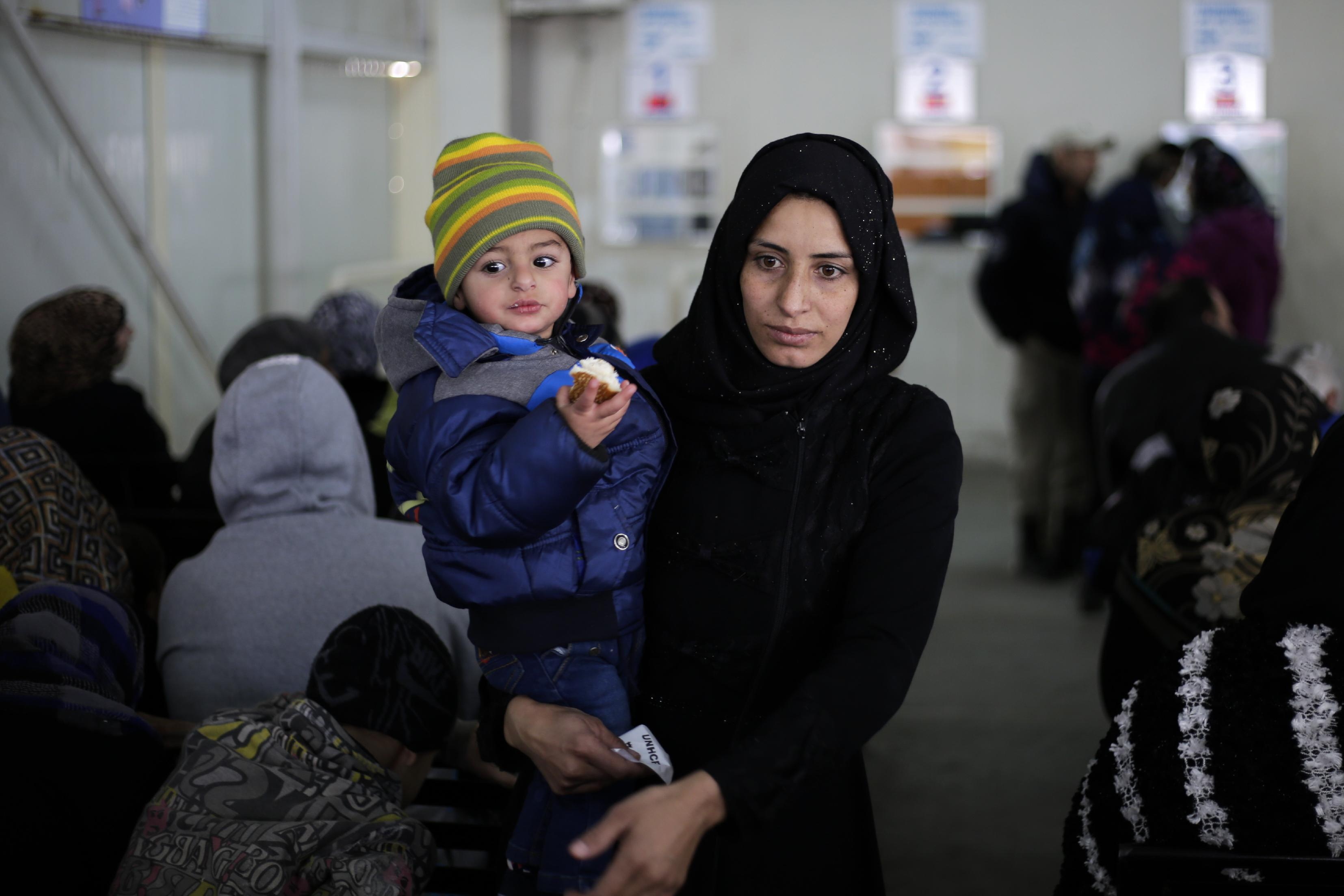 A Syrian boy eats bread as waits in line with his mother as hundred of Syrian families wait to register at the United Nations High Commissioner for Refugees headquarters, in Beirut, Lebanon, Monday, Jan. 30, 2017. By executive order, U.S. President Donald Trump imposed a 90-day ban, Friday, that affects travel to the U.S. by citizens of Iraq, Syria, Iran, Sudan, Libya, Somalia and Yemen and puts an indefinite hold on a program resettling Syrian refugees. (AP Photo/Hassan Ammar)