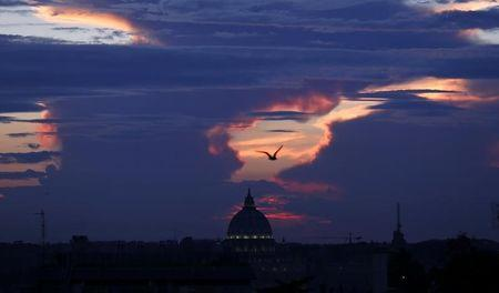 Saint Peter's square is silhouetted during a sunset in Rome