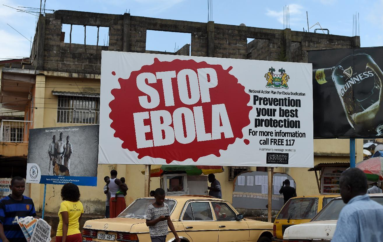 People walk past a billboard with a message about Ebola in Freetown, Sierra Leone on November 7, 2014
