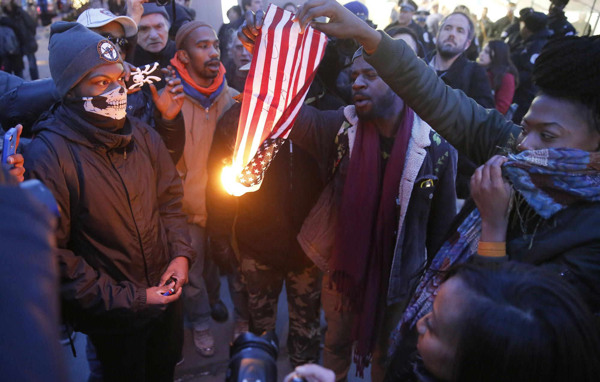 <p>Protesters burn an American flag outside the Apple store on Chicago's Magnificent Mile in a continued protest against Chicago police, the mayor and state's attorney Tuesday, Feb. 23, 2016, in Chicago. (AP Photo/Charles Rex Arbogast) </p>