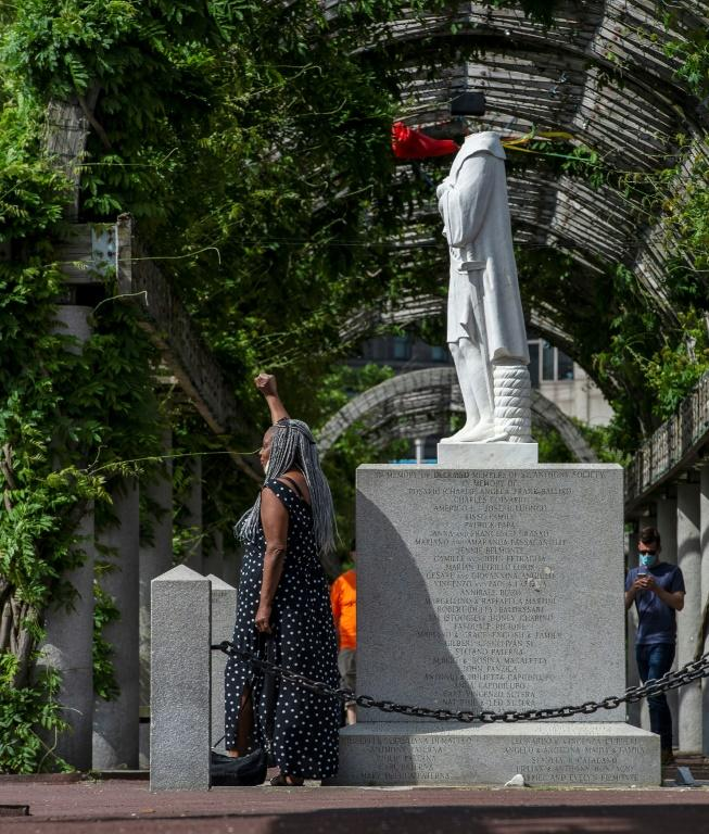A woman poses in front of a decapitated statue of Columbus at Christopher Columbus Park in Boston, Massachusetts on June 10 (AFP Photo/Joseph Prezioso)