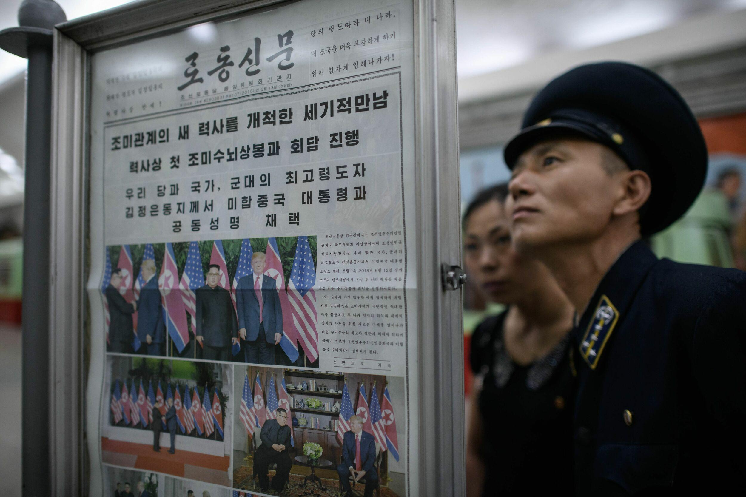 TOPSHOT - A conductor reads the latest edition of the Rodong Sinmun newspaper showing images of North Korean leader Kim Jong Un meeting with US president Donald Trump during their summit in Singapore, at a news stand on a subway platform of the Pyongyang metro on June 13, 2018. - Donald Trump accepted an invitation from Kim Jong Un to visit North Korea during their historic summit, Pyongyang state media reported on June 13, as the US president said the world had jumped back from the brink of 'nuclear catastrophe'. (Photo by Ed JONES / AFP)        (Photo credit should read ED JONES/AFP/Getty Images)
