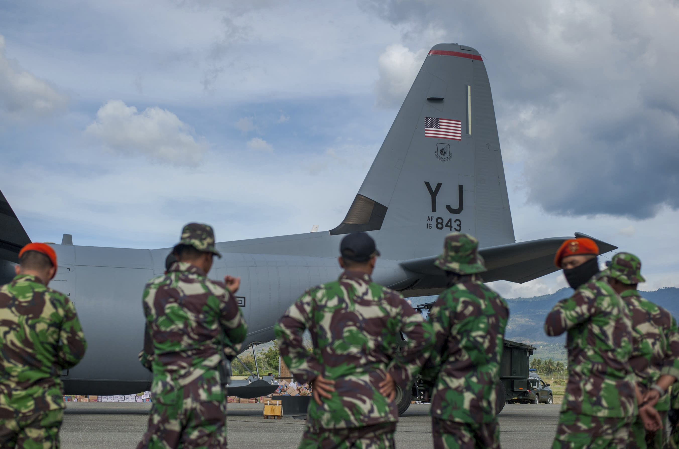 Indonesian soldiers stand near a U.S. Air Force cargo plane delivering relief goods at Mutiara Sis Al-Jufrie Airport in Palu, Central Sulawesi, Indonesia, Sunday, Oct. 7, 2018. Indonesia's disaster agency said the number of dead had climbed and many more people could be buried, especially in the Palu neighborhoods of Petobo and Balaroa, where thousands of homes were damaged or sucked into deep mud when the Sept. 28 quake caused loose soil to liquefy. (AP Photo/Fauzy Chaniago)