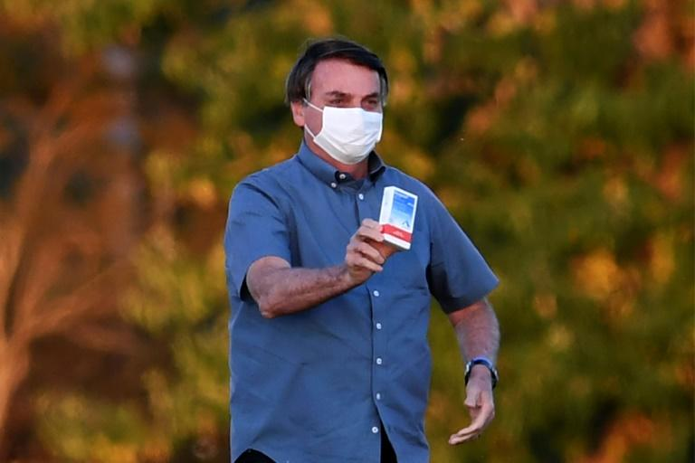 Brazilian President Jair Bolsonaro, seen here showing off a box of the drug hydroxychloroquine to supporters outside presidential palace in Brasilia, said nearly everyone will probably get the coronavirus, just like he did