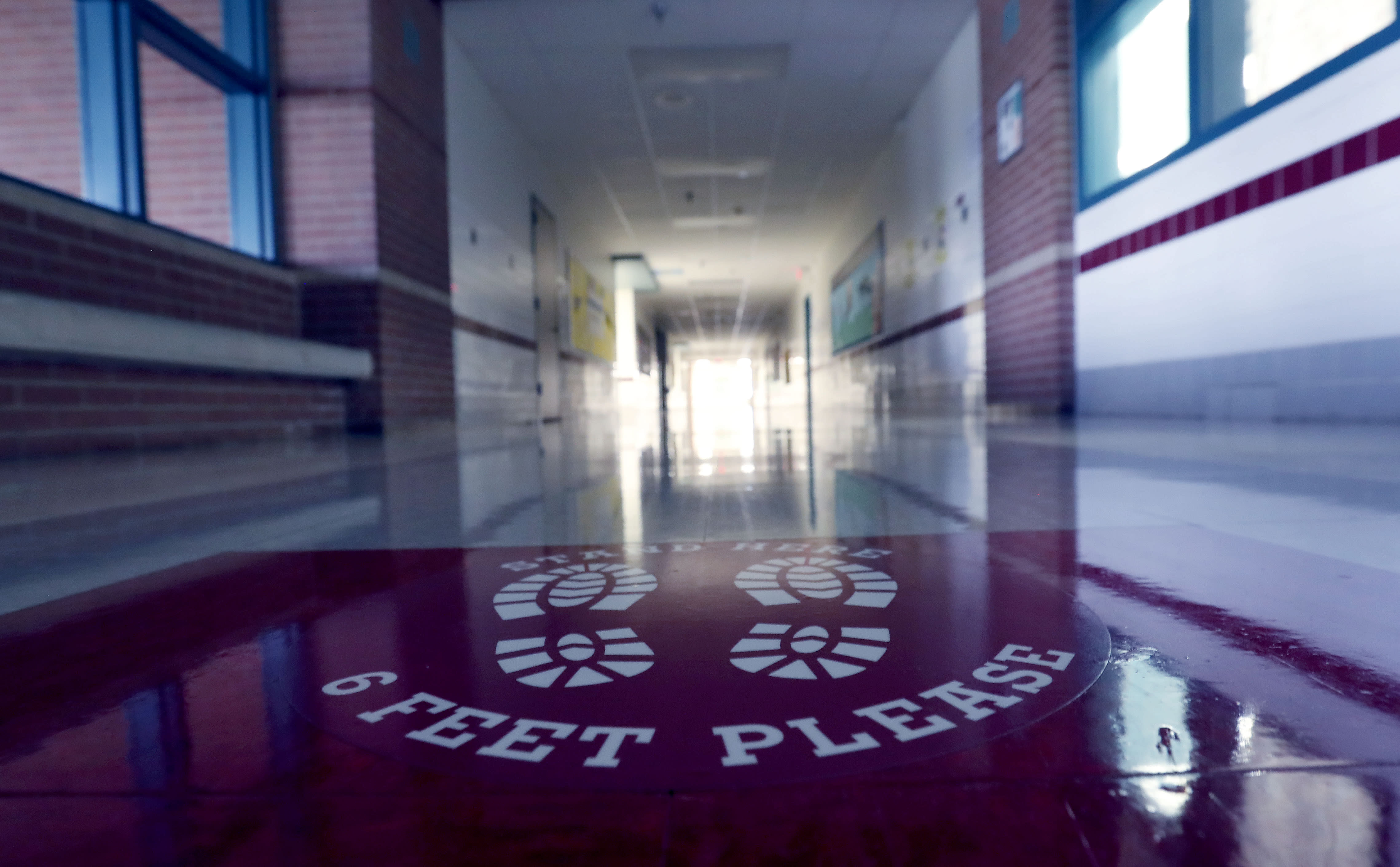 A social distancing reminder sits on the floor of an empty hallway at Stephens Elementary School in Rowlett, Texas, Wednesday, July 22, 2020.(AP Photo/LM Otero)
