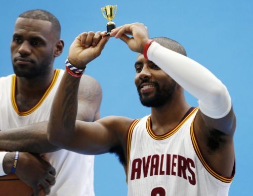 Kyrie Irving raises a tiny trophy as LeBron James looks uncomfortable. (AP)