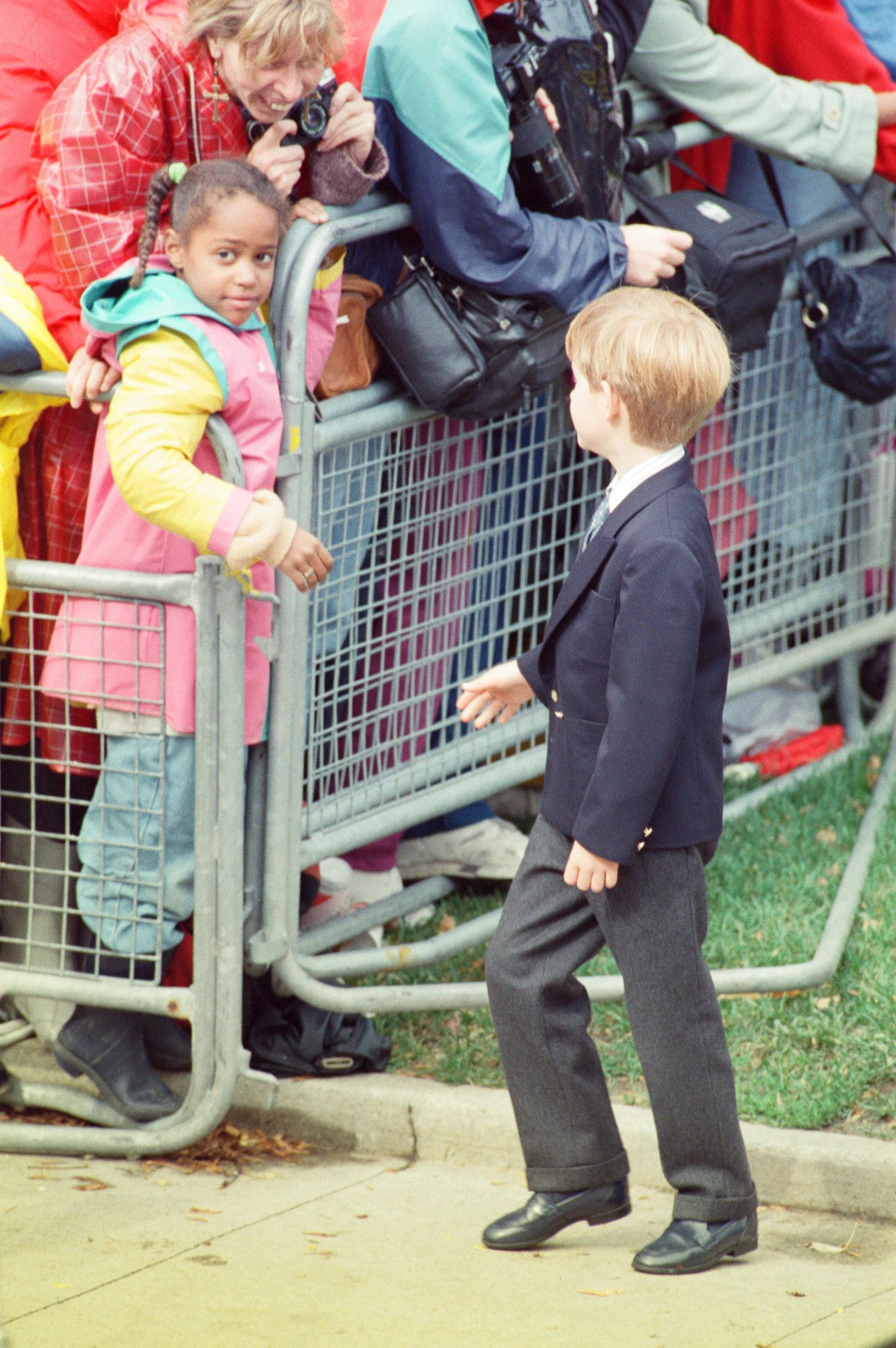 Princess Diana, Princess of Wales, with her sons William and Harry on a walkabout after church service at St. James Cathedral in Toronto, Canada. Picture shows Prince Harry talking to a young lady who has come out to see the Royal family. Picture taken 27th October 27, 1991. (Photo by Kent Gavin/Mirrorpix/Getty Images)