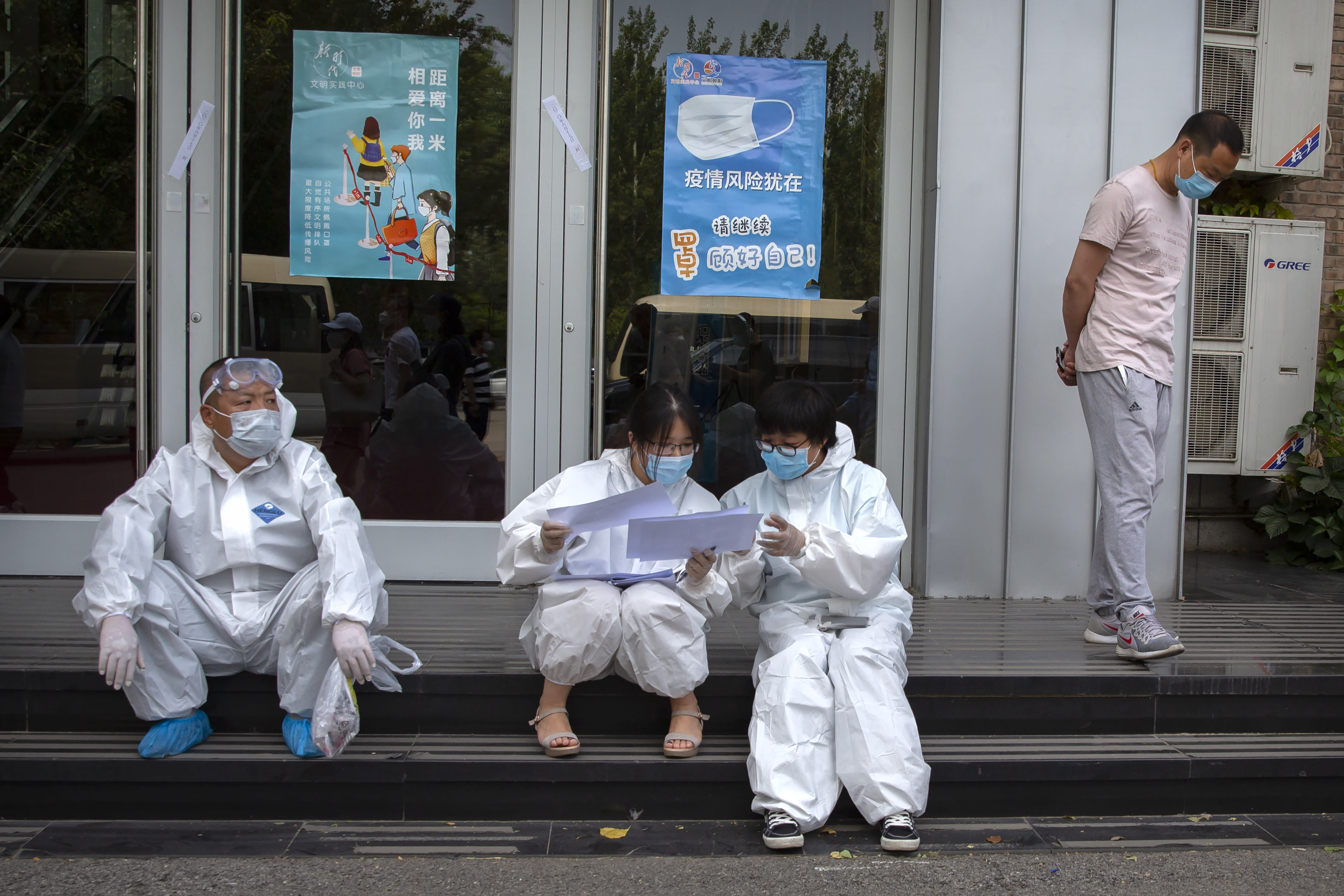 Workers in protective suits review paperwork at a COVID-19 testing site for those who were potentially exposed to the coronavirus outbreak at a wholesale food market in Beijing, Wednesday, June 17, 2020. As the number of cases of COVID-19 in Beijing climbed in recent days following an outbreak linked to a wholesale food market, officials announced they had identified hundreds of thousands of people who needed to be tested for the coronavirus. (AP Photo/Mark Schiefelbein)