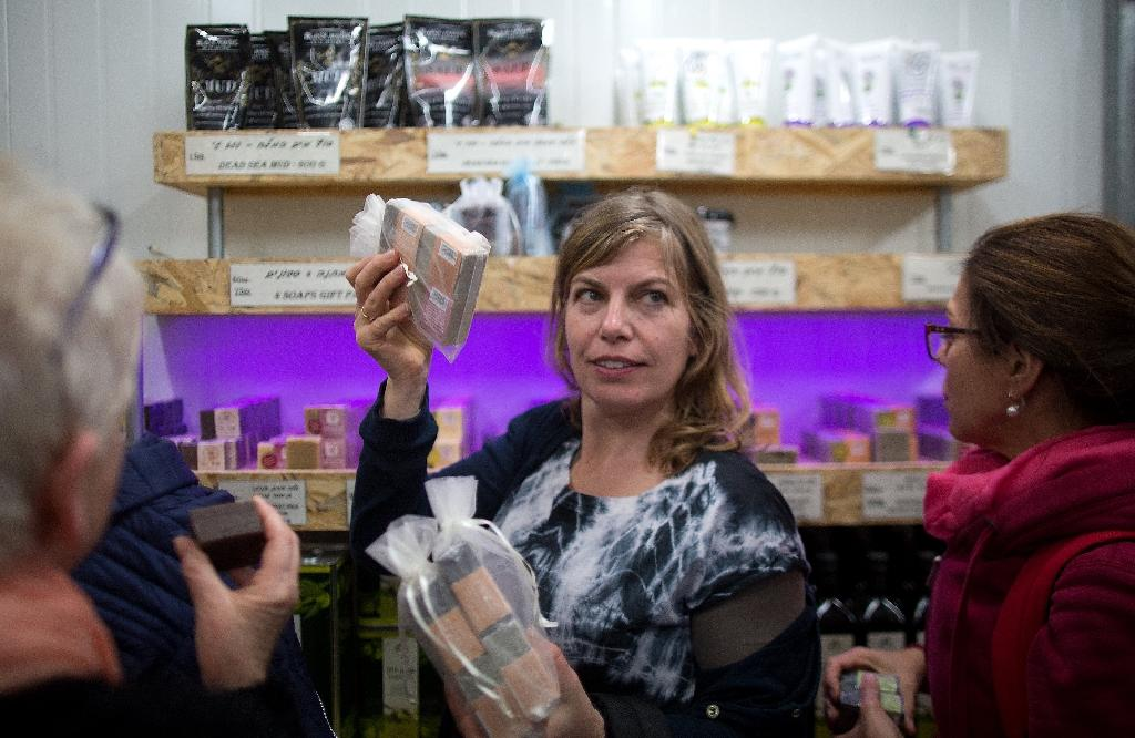 Dutch tourists inspect soaps produced in the Israeli settlement of Kohav Hashahar, during a tour organized by the Lev Haolam foundation, on November 10, 2015 (AFP Photo/Menahem Kahana)