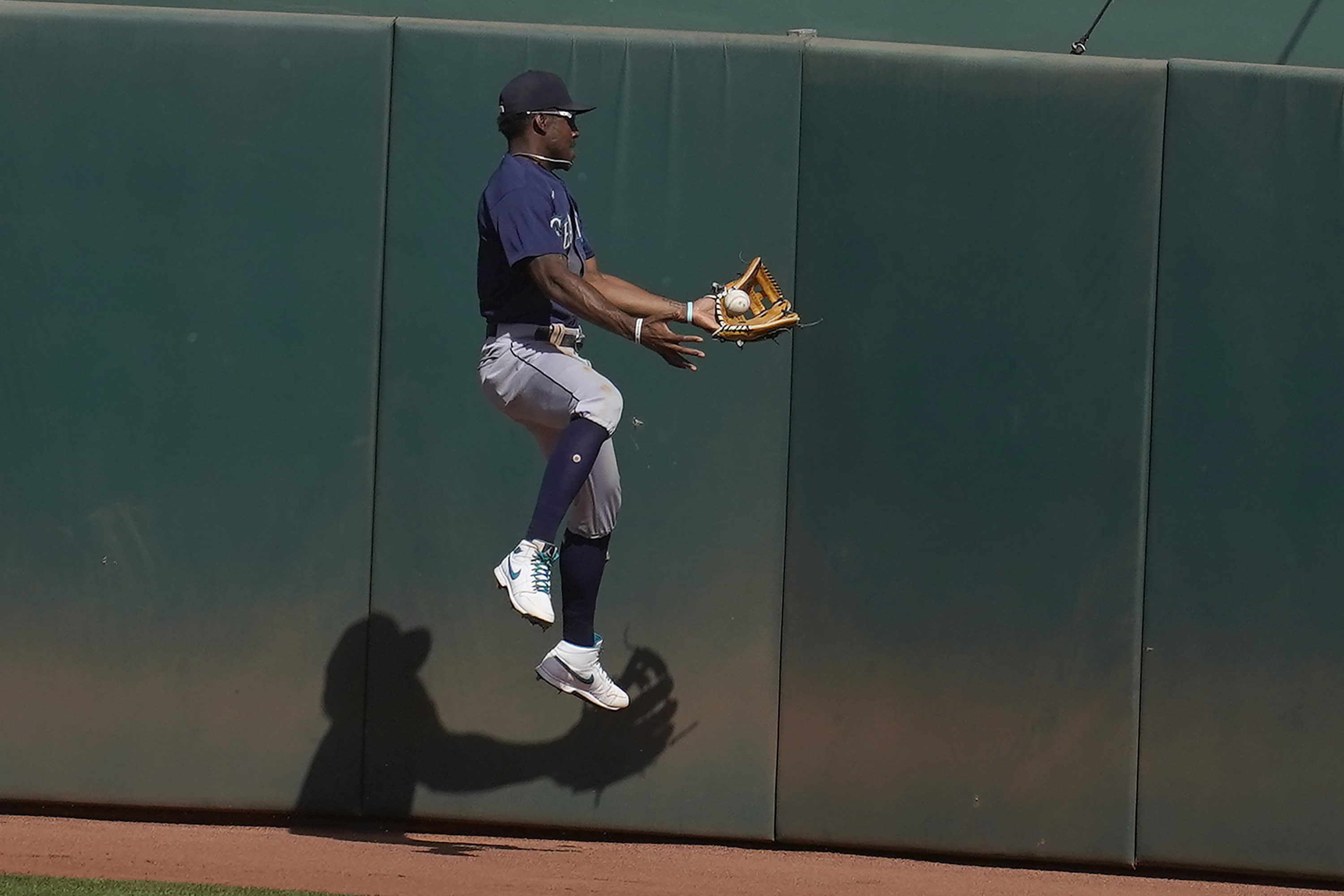 Seattle Mariners center fielder Kyle Lewis cannot catch a two-run double hit by Oakland Athletics' Mark Canha during the seventh inning of a baseball game in Oakland, Calif., Sunday, Sept. 27, 2020. (AP Photo/Jeff Chiu)
