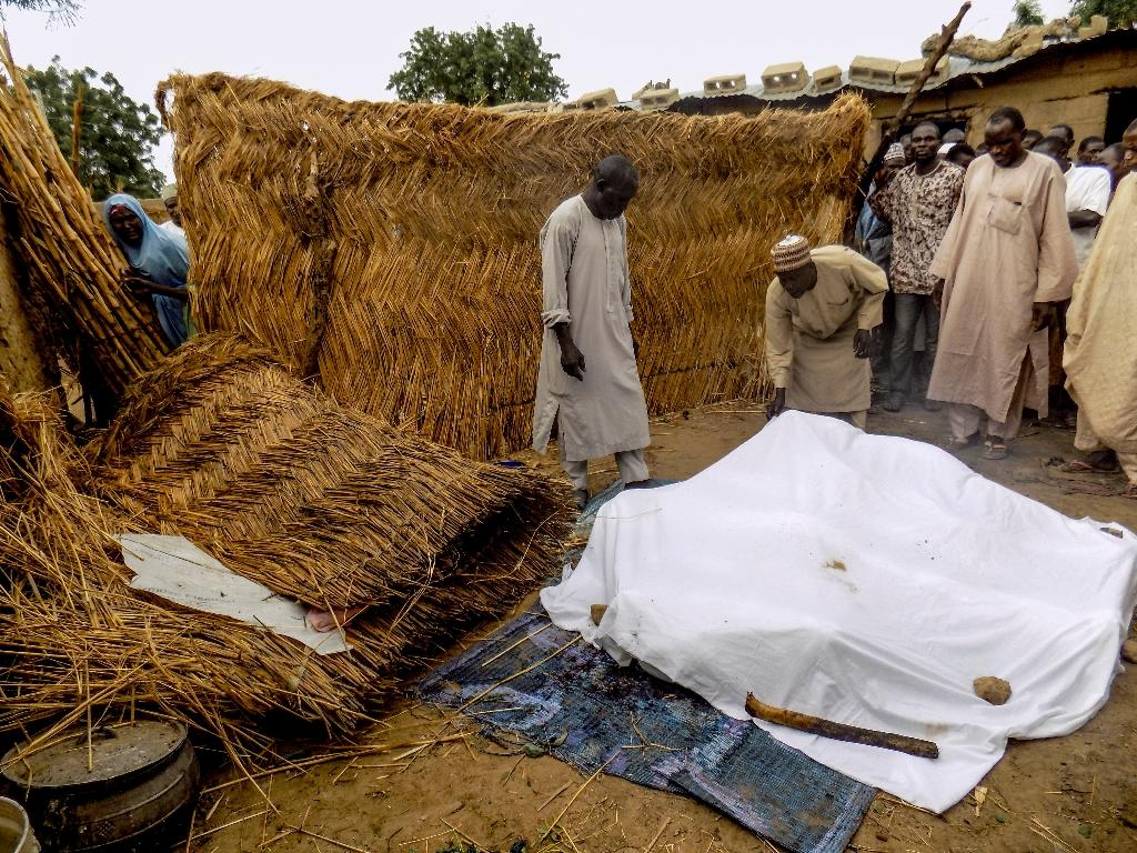 Residents cover victims of a Boko Haram suicide bombing attack in Koffa, northern Nigeria, on June 19, 2017 (AFP Photo/-)