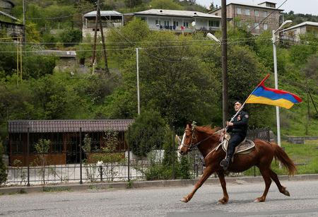 A man holds an Armenian flag as he rides a horse before a rally held by supporters of opposition leader Nikol Pashinyan in the town of Ijevan, Armenia April 28, 2018. REUTERS/Gleb Garanich