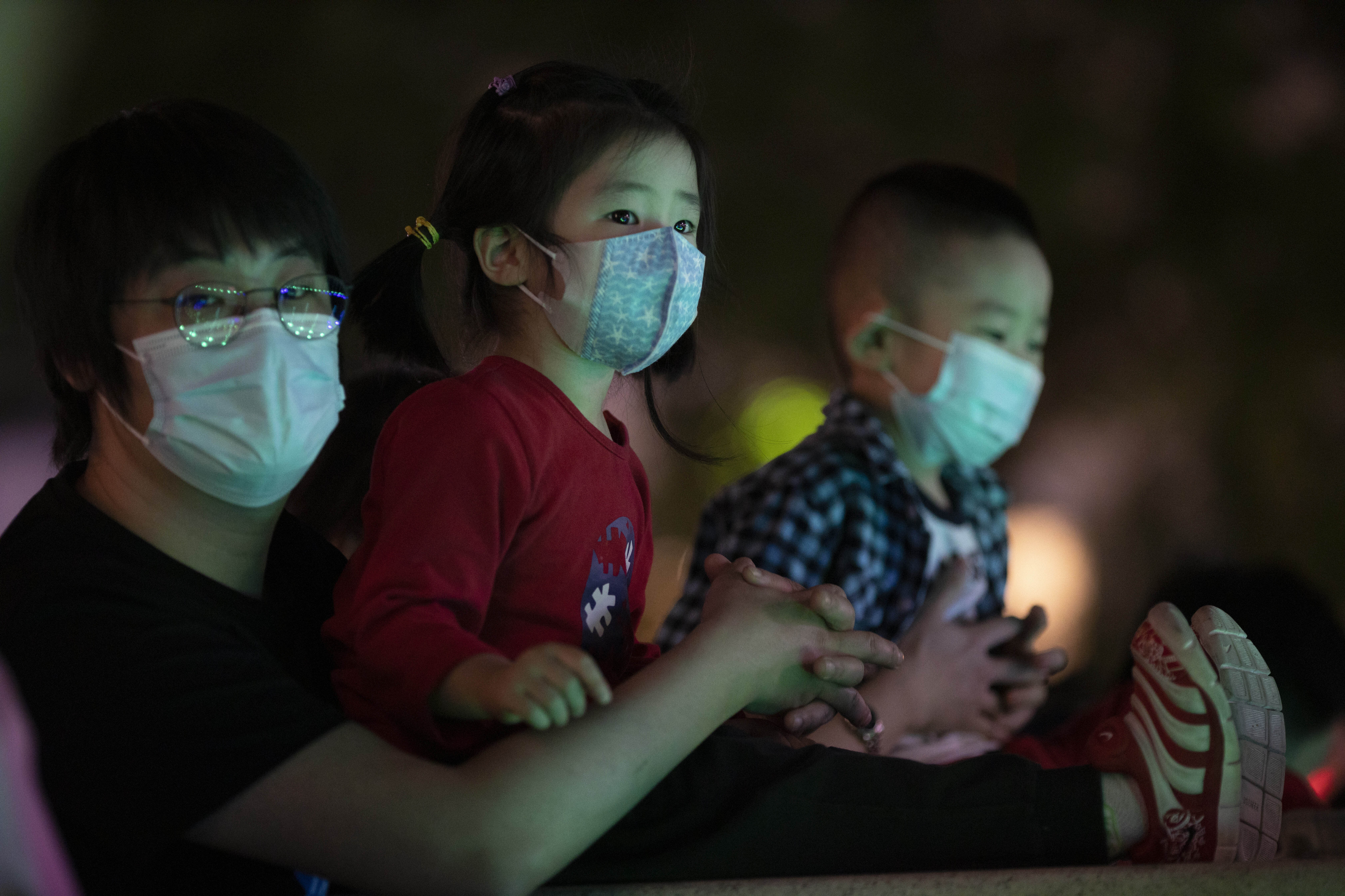 Residents wearing masks to curb the spread of the new coronavirus enjoy a cool evening near a water fountain in Beijing on Sunday, May 24, 2020. (AP Photo/Ng Han Guan)