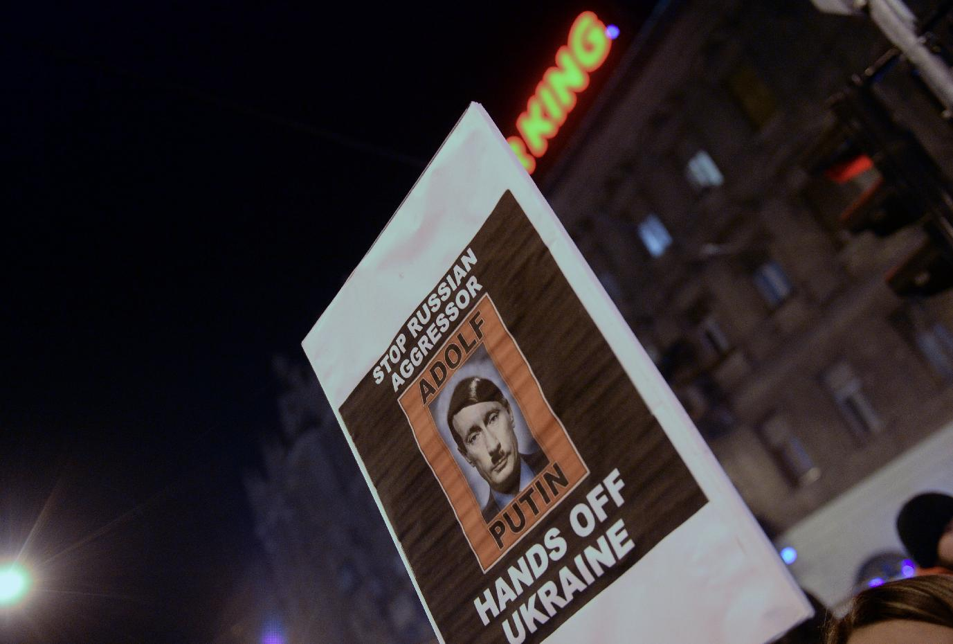 """Protesters hold a banner, """"Stop Russian aggressor Adolf Putin Hands off Ukraine"""" during a demonstration on February 16, 2015 in Budapest (AFP Photo/Attila Kisbenedek)"""