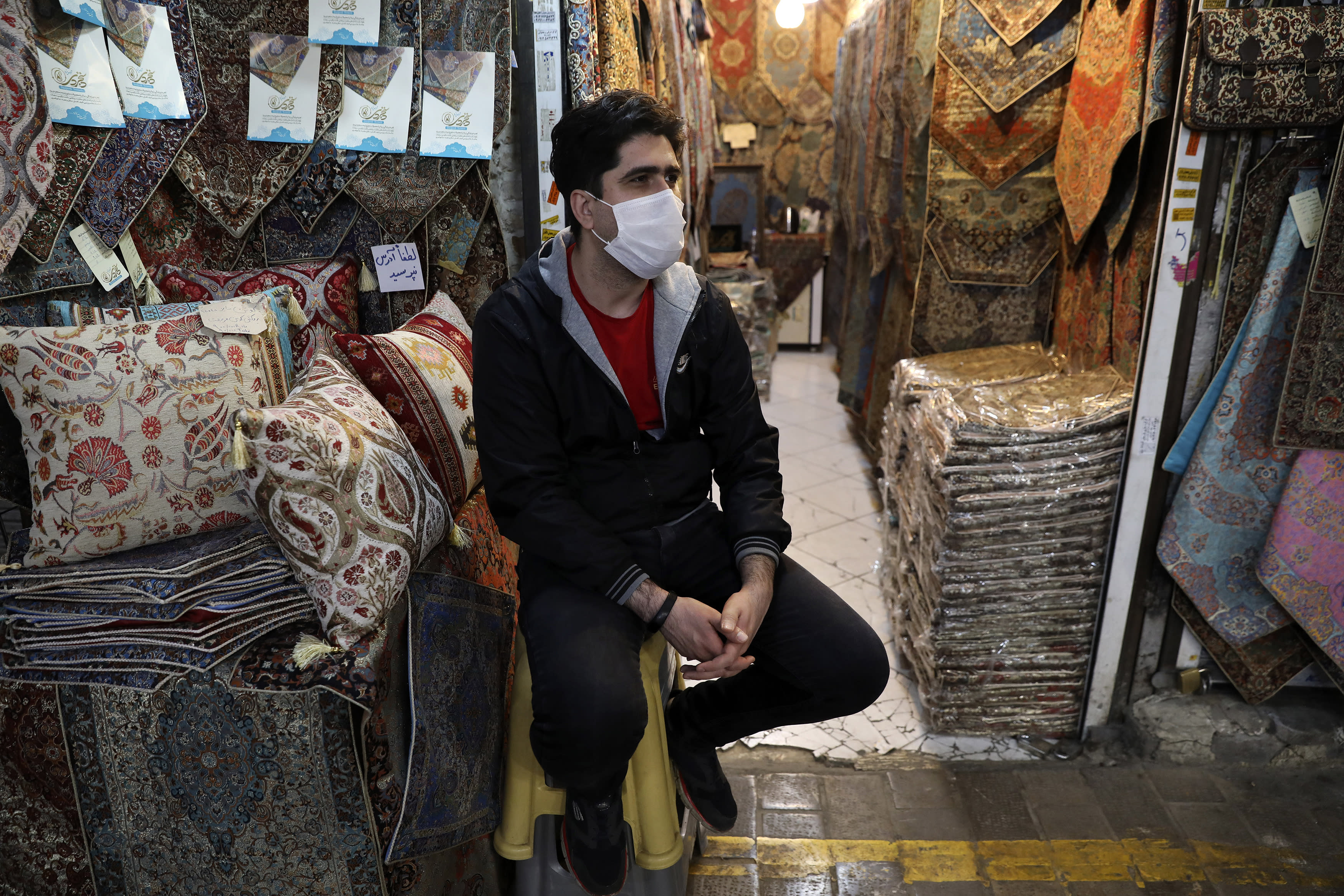 In this Tuesday, March 17, 2020, photo, a shopkeeper wearing a face mask to help protect against the new coronavirus, waits for customers at the Tehran's Grand Bazaar, Iran. The new coronavirus ravaging Iran is cutting into celebrations marking the Persian New Year, known as Nowruz. (AP Photo/Vahid Salemi)