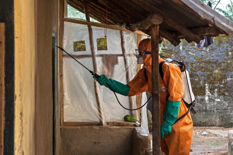 A volunteer in protective suit sprays disinfectant outside a home in Waterloo, Sierra Leone, on October 7, 2014 (AFP Photo/Florian Plaucheur)