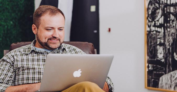 Stock image of a man using an Apple laptop.