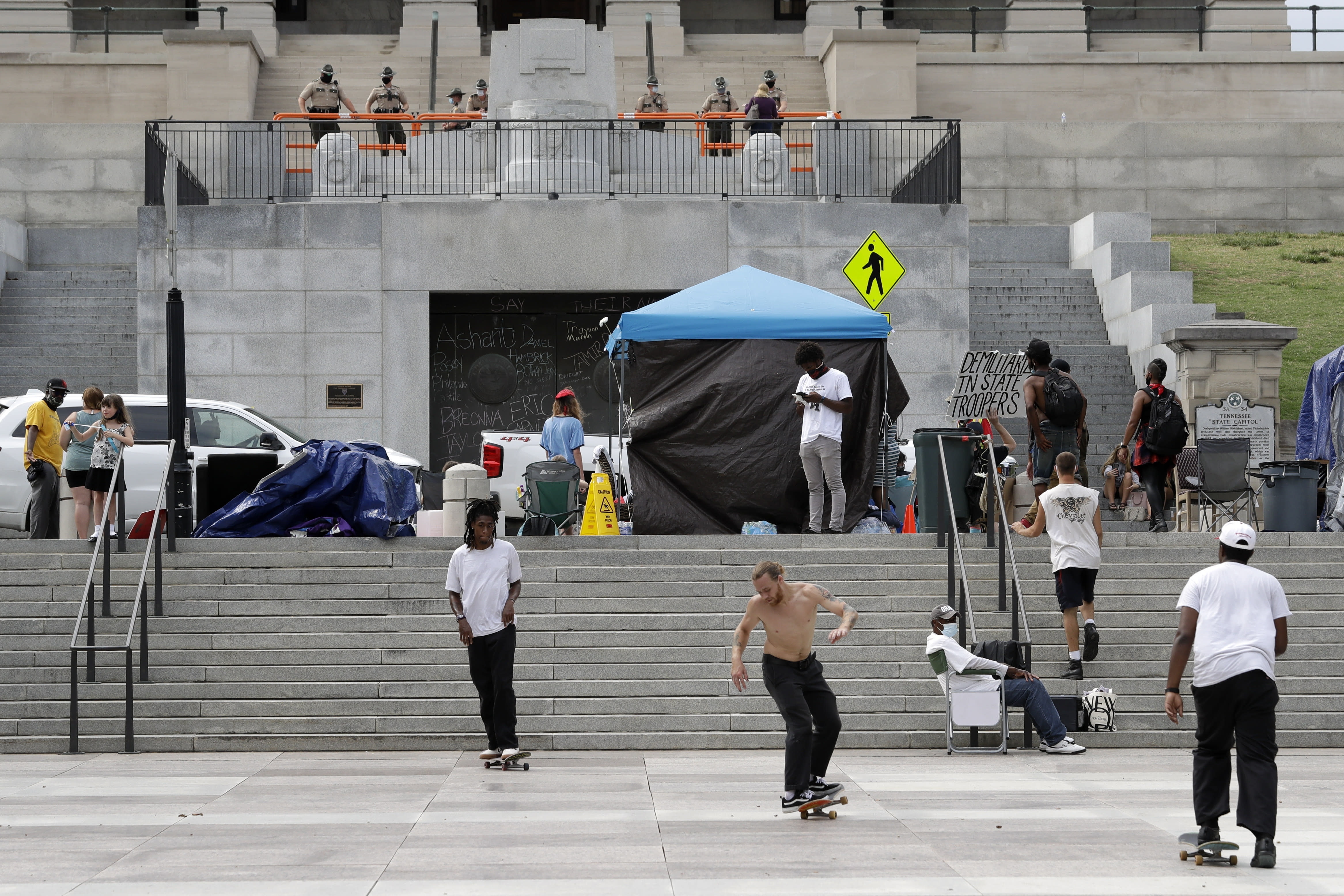 Demonstrators protest across the street from the Capitol as state troopers watch Wednesday, July 1, 2020, in Nashville, Tenn. Tennessee's newest law, a wide range of crimes commonly associated with protests will see a big bump in penalties and fines, but the most contentious element focuses on escalated penalties for illegal camping. Violators will now face a Class E felony, punishable by up to six years in prison. (AP Photo/Mark Humphrey)