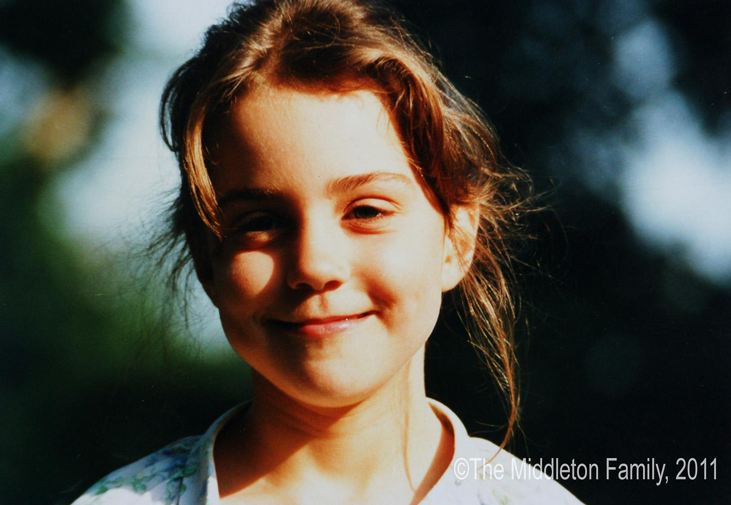 An adorable Kate smiles at the camera, age five.