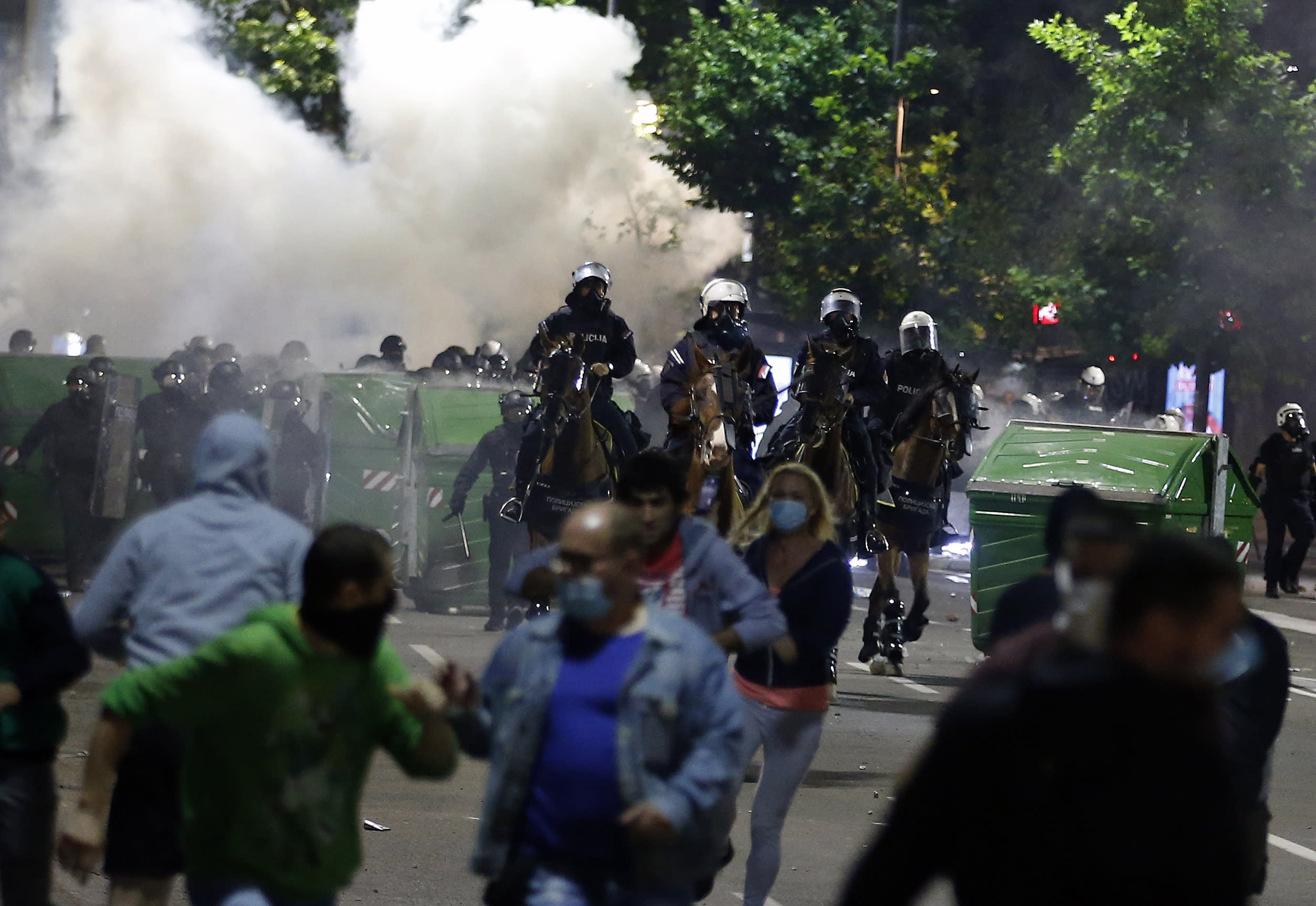 Sebian police officers disperse protesters in front of Serbian parliament building in Belgrade, Serbia, Wednesday, July 8, 2020. Thousands of people protested the Serbian president's announcement that a lockdown will be reintroduced after the Balkan country reported its highest single-day death toll from the coronavirus Tuesday. (AP Photo/Darko Vojinovic)