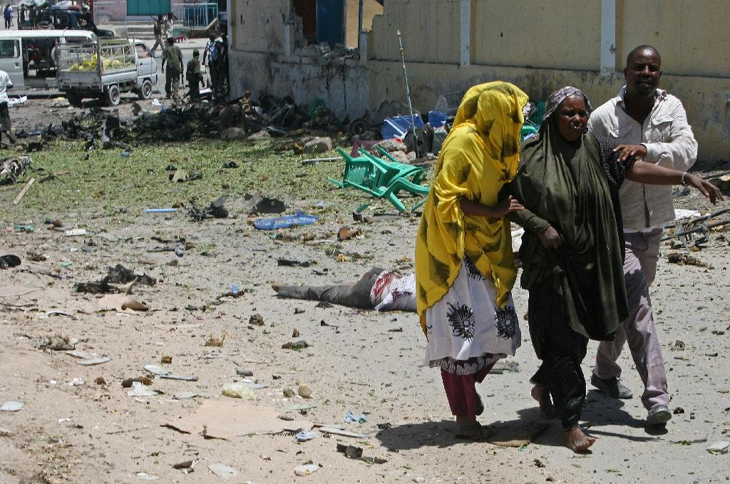 A wounded woman is helped at the scene of a car bomb outside the Education Ministry in Mogadishu on April 14, 2015 (AFP Photo/Mohamed Abdiwahab)
