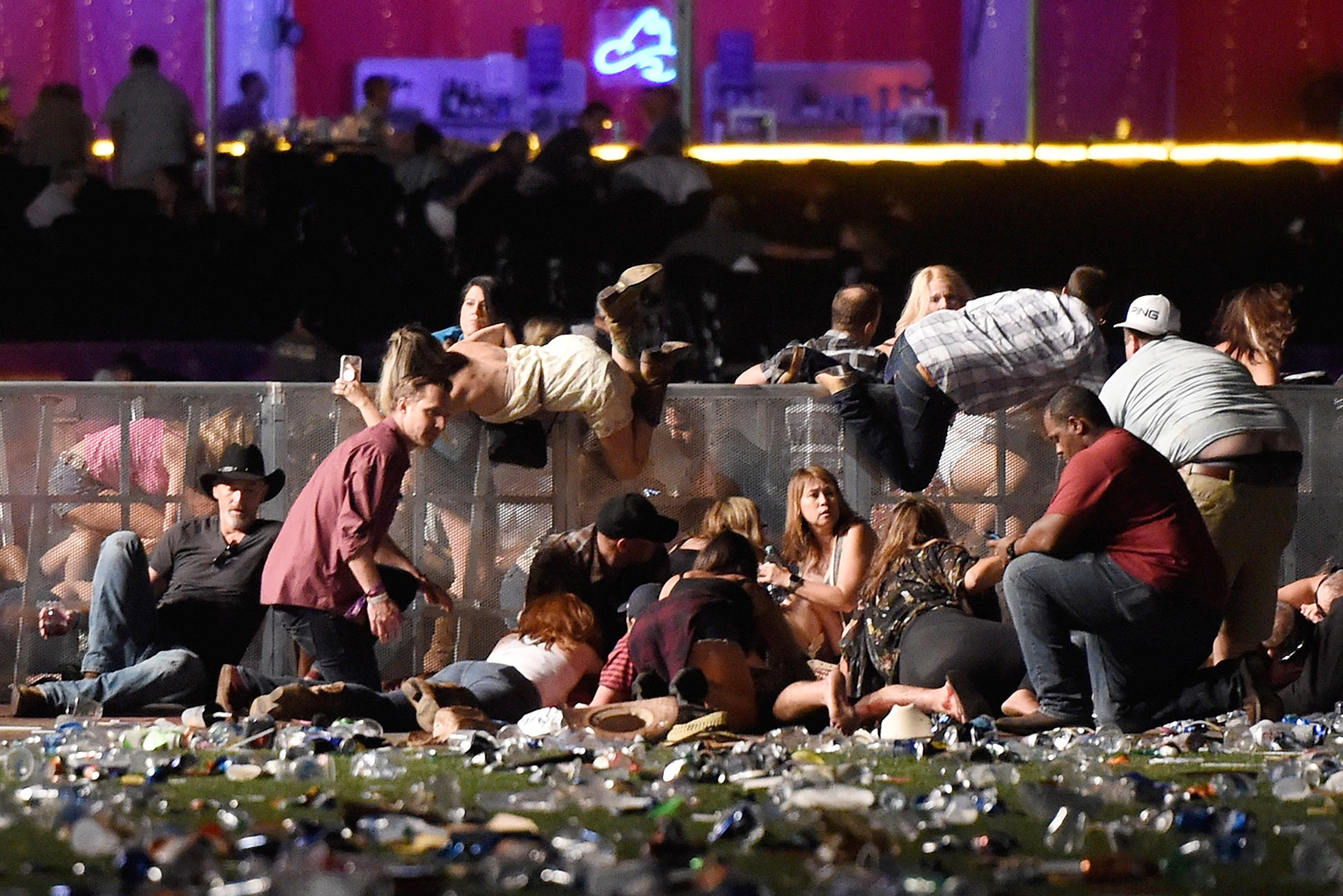 Music fans duck and cover at the Route 91 Harvest country music festival. (Photo: David Becker/Getty Images)