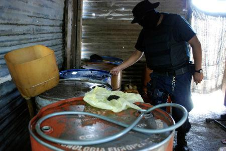 FILE PHOTO: Policeman inspects barrels containing stolen diesel fuel, stored in a tyre repair shop, during an operation in the municipality of Apodaca
