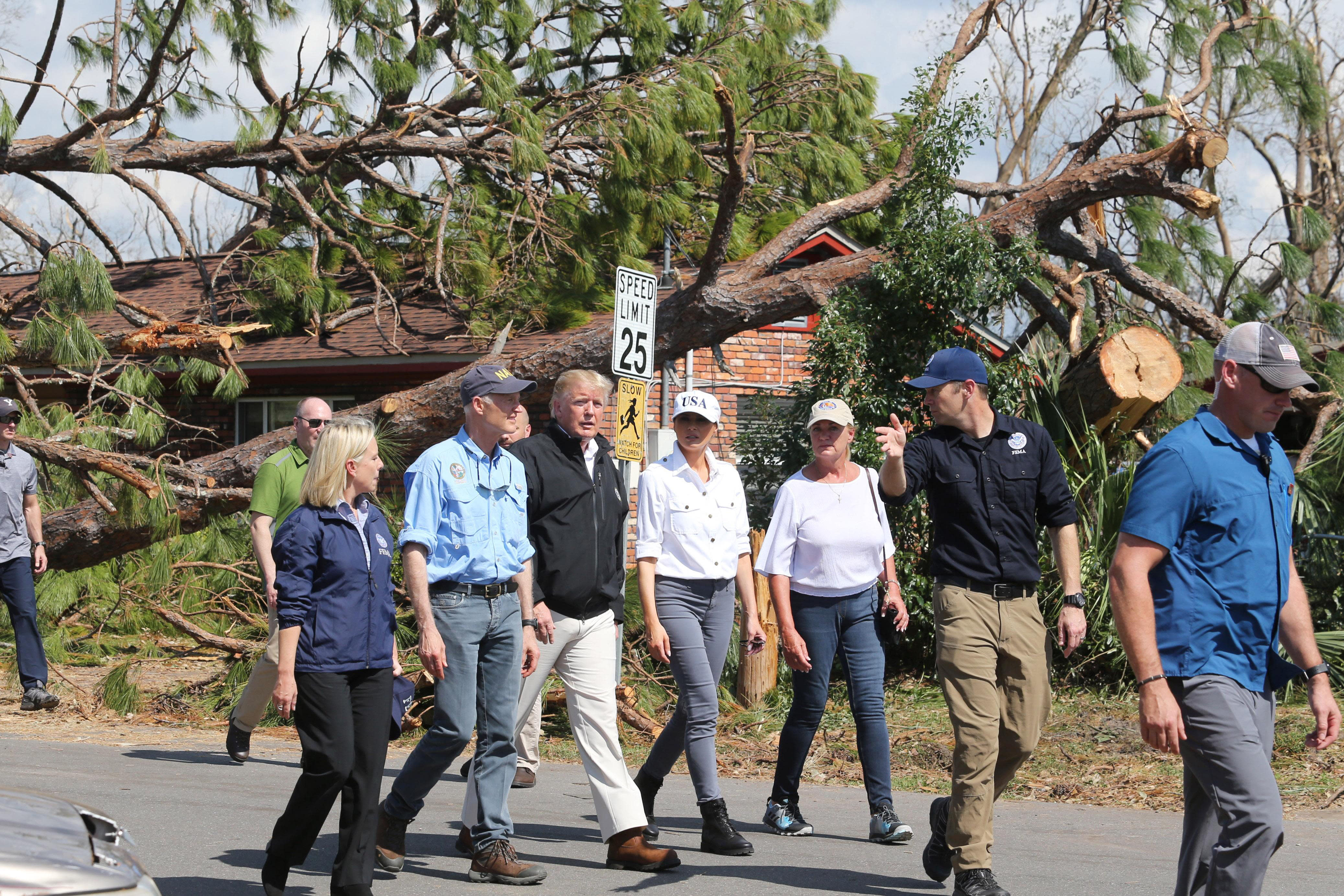 Florida Gov. Rick Scott, second from left, President Donald J Trump, center left, Melania Trump, center right, and Lynn Haven, Fla., Mayor Margo Anderson walk through a neighborhood in the storm-ravaged city Monday Oct. 15, 2018. (Michael Snyder/Northwest Florida Daily News via AP)
