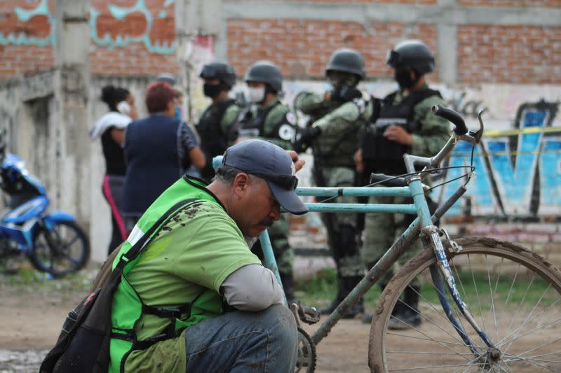 A man sits as soldiers keep watch outside a drug rehabilitation facility where assailants killed several people, according to Guanajuato state police, in Irapuato