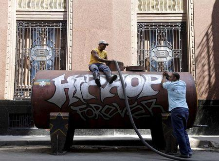 Workers stand next to a water tank used to supply water to residents in Havana in this April 13, 2011 file photo. REUTERS/Enrique De La Osa/Files
