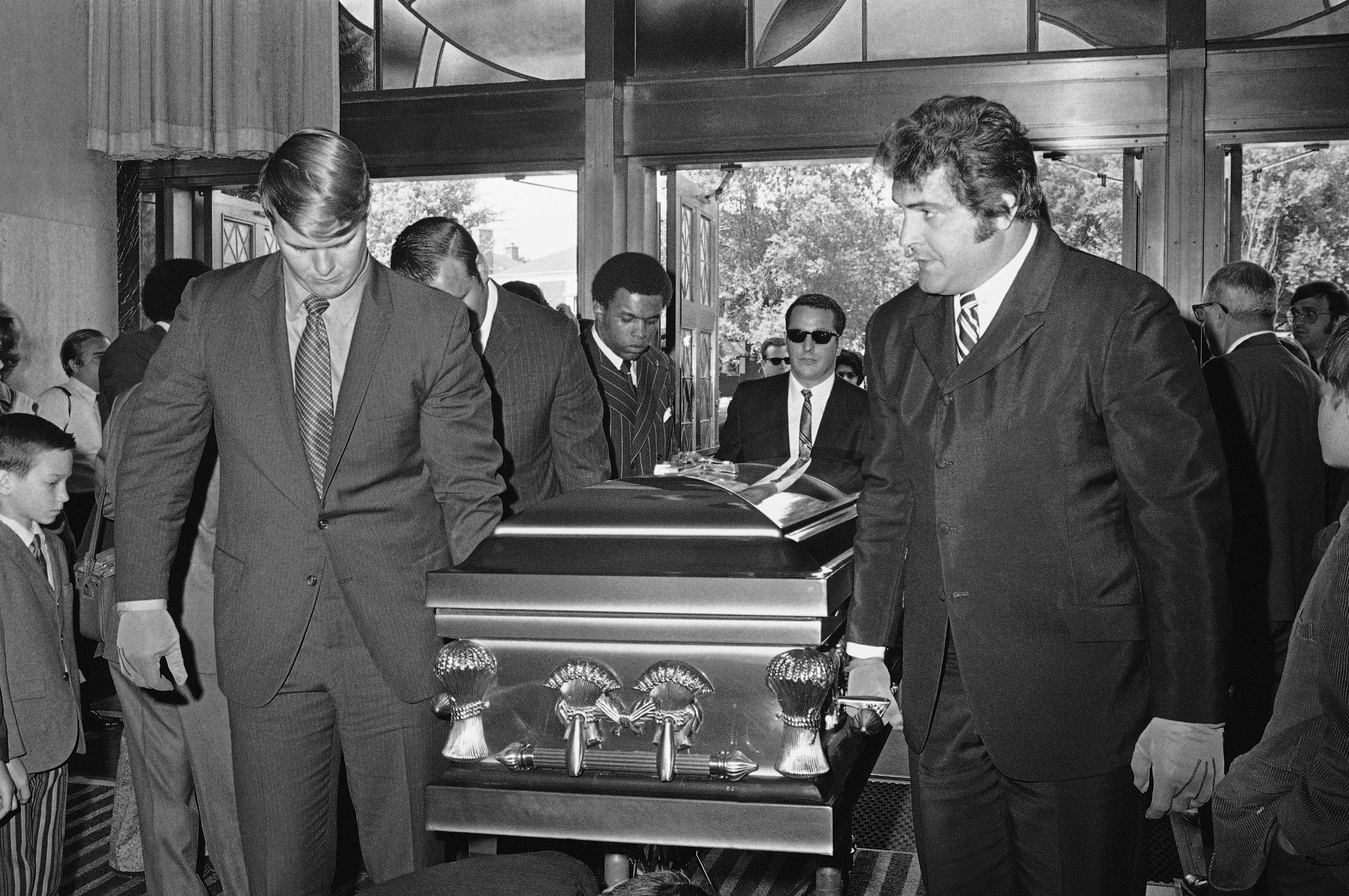 """FILE - In this June 19, 1970, file photo. Chicago Bears teammates of Brian Piccolo carry his coffin into Christ the King Church for funeral services in Chicago. From left, front to back, are Randy Jackson, Dick Butkus, and Gale Sayer. Ed O'Bradovich is at right. Hall of Famer Gale Sayers, who made his mark as one of the NFL's best all-purpose running backs and was later celebrated for his enduring friendship with a Chicago Bears teammate with cancer, has died. He was 77. Nicknamed """"The Kansas Comet"""" and considered among the best open-field runners the game has ever seen, Sayers died Wednesday, Sept. 23, 2020, according to the Pro Football Hall of Fame. (AP Photo/File)"""