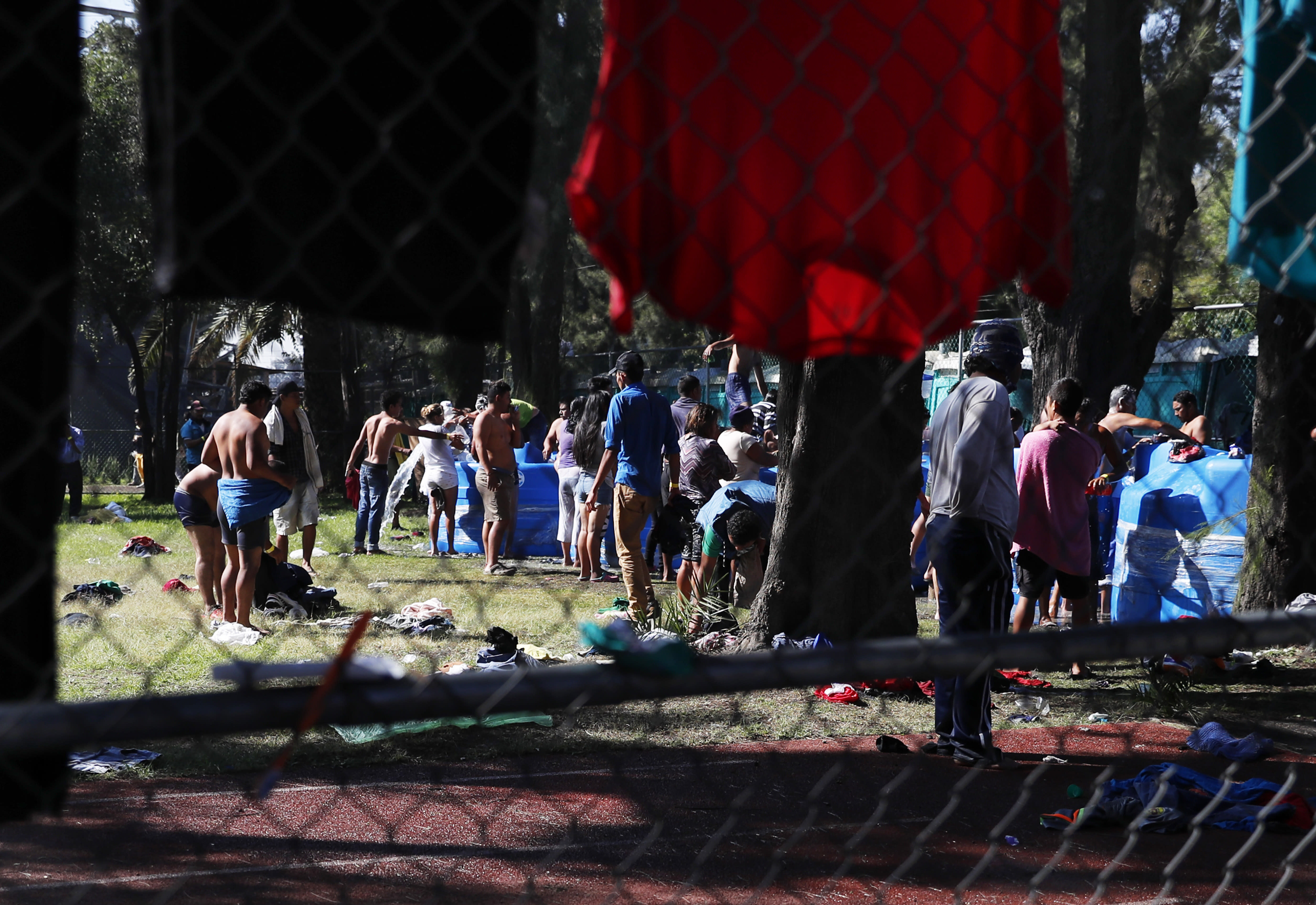 Central American migrants line up in front of water tanks at the Jesus Martinez stadium in Mexico City, Tuesday, Nov. 6, 2018. Humanitarian aid converged around the stadium in Mexico City where thousands of Central American migrants winding their way toward the United States were resting Tuesday after an arduous trek that has taken them through three countries in three weeks. (AP Photo/Marco Ugarte)
