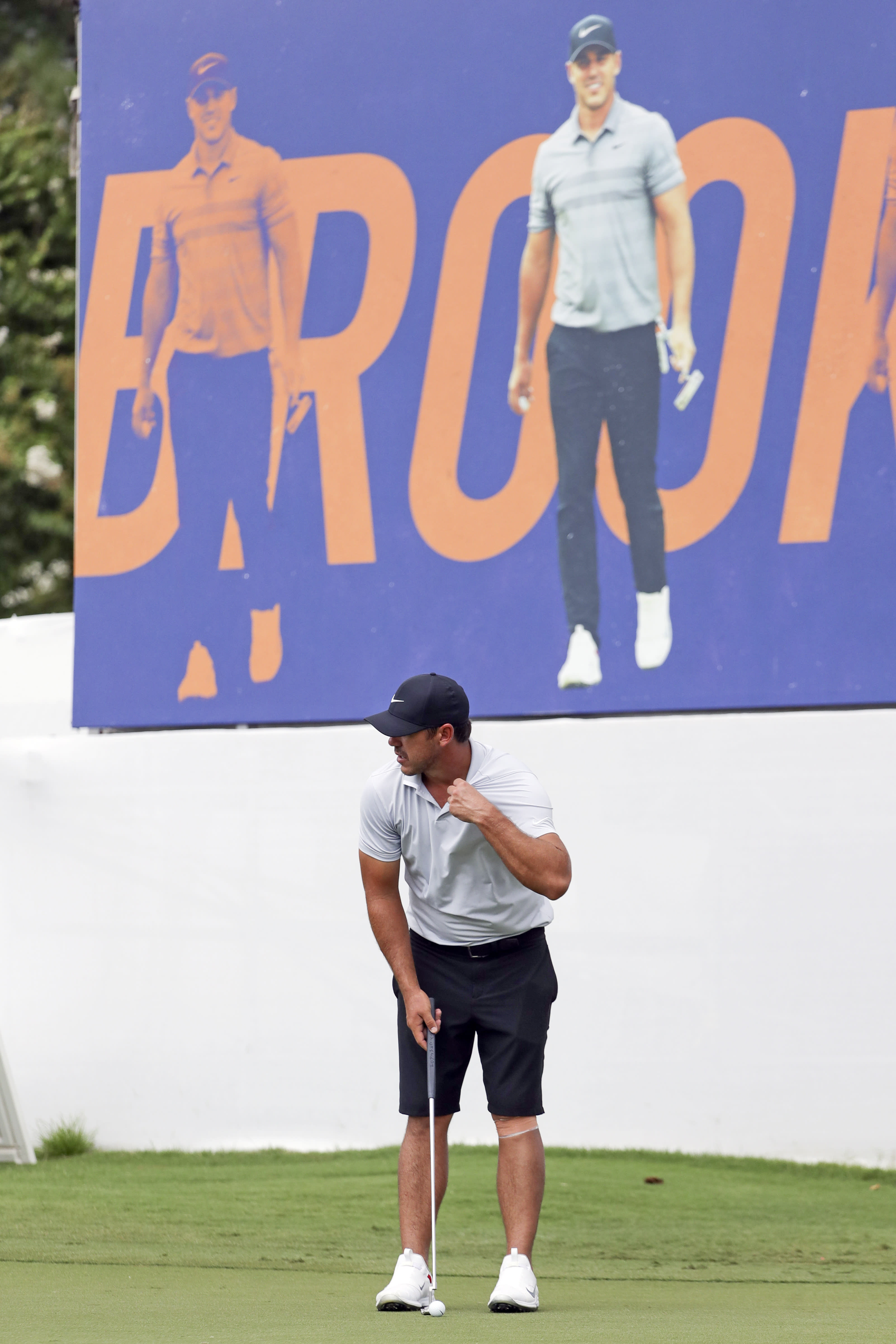 Brooks Koepka putts on the practice green under a banner with his picture at the World Golf Championship-FedEx St. Jude Invitational Wednesday, July 29, 2020, in Memphis, Tenn. Koepka, who won three times last year is trying to defend his FedEx St. Jude Invitational title with an injured left knee that has had him putting more weight on his right leg and affecting his game. (AP Photo/Mark Humphrey)