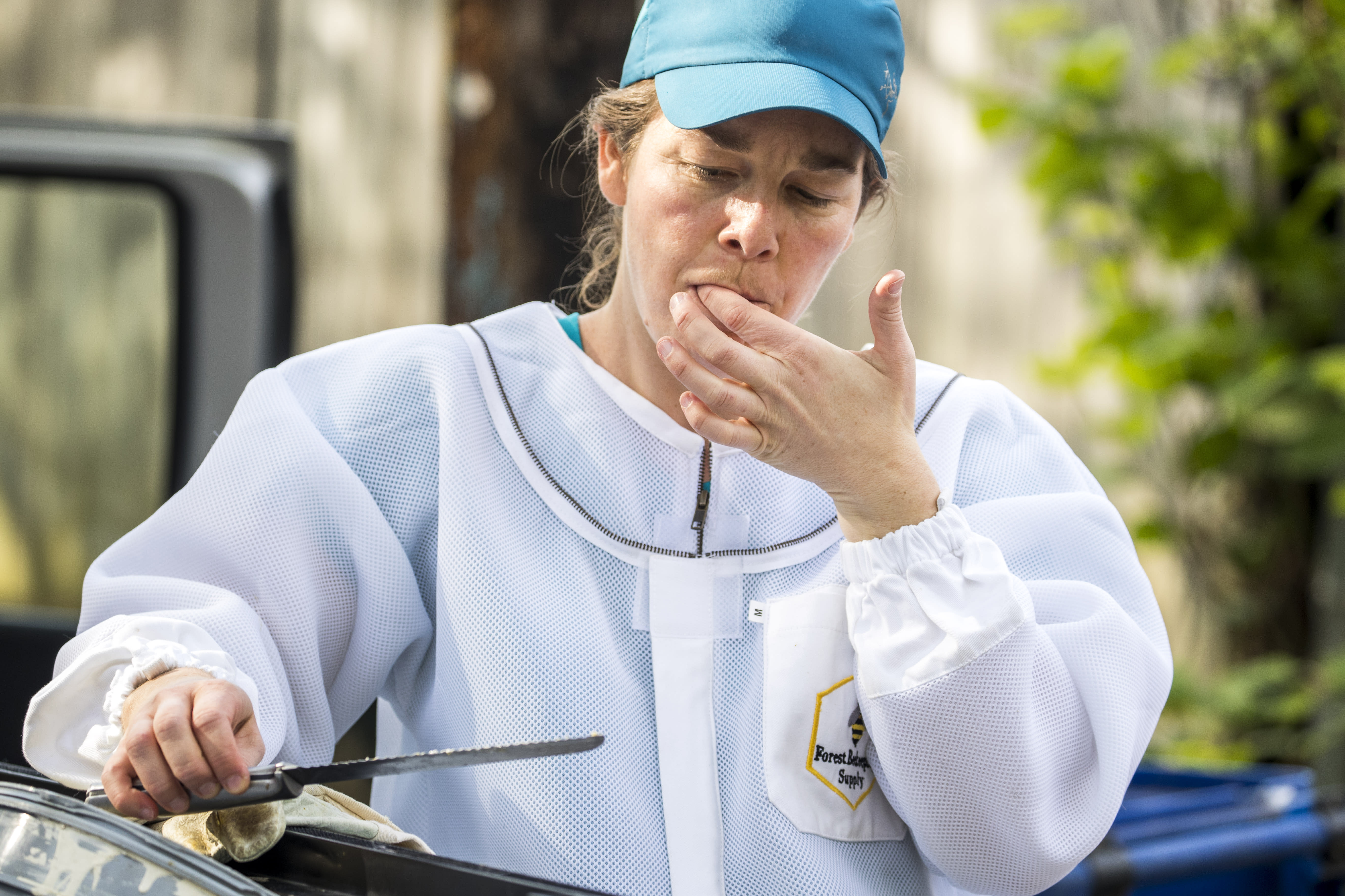 Beekeeper Erin Gleeson licks honey from a knife after helping to remove a swarm of honeybees from a fence line in a neighborhood in Anacostia, Monday, April 20, 2020, in Washington. (AP Photo/Andrew Harnik)