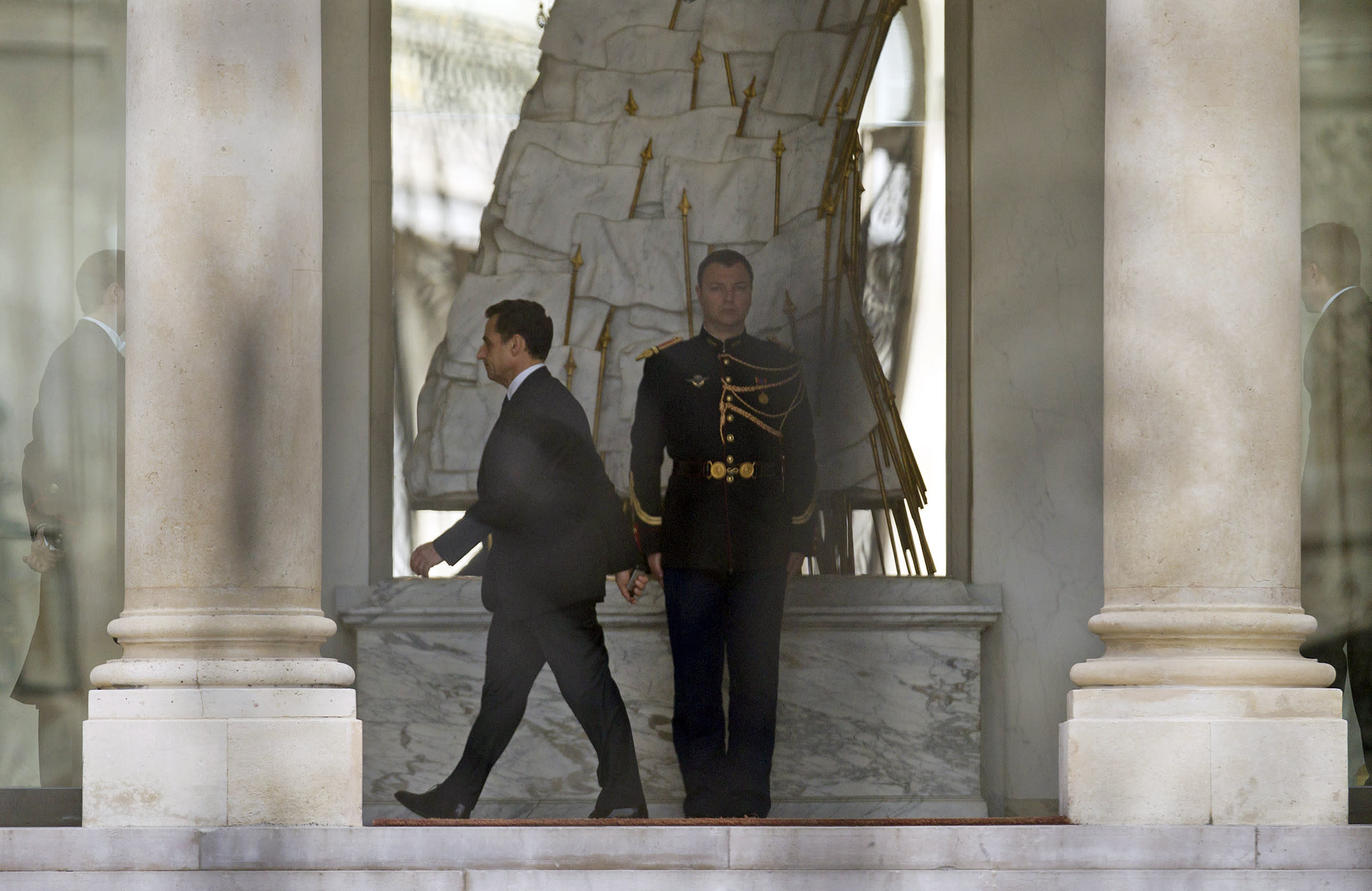 Outgoing French President Nicolas Sarkozy walks along the hallway at Elysee palace in Paris, Monday May 7, 2012. France handed the presidency to leftist Francois Hollande, a champion of government stimulus programs who says the state should protect the downtrodden, a victory that could deal a death blow to the drive for austerity that has been the hallmark of Europe in recent years. (AP Photo/Jacques Brinon)