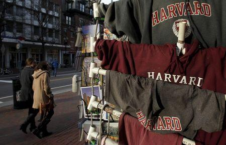 People walk past Harvard University t-shirts for sale in Harvard Square in Cambridge, Massachusetts in this November 16, 2012 file photo. REUTERS/Jessica Rinaldi/Files