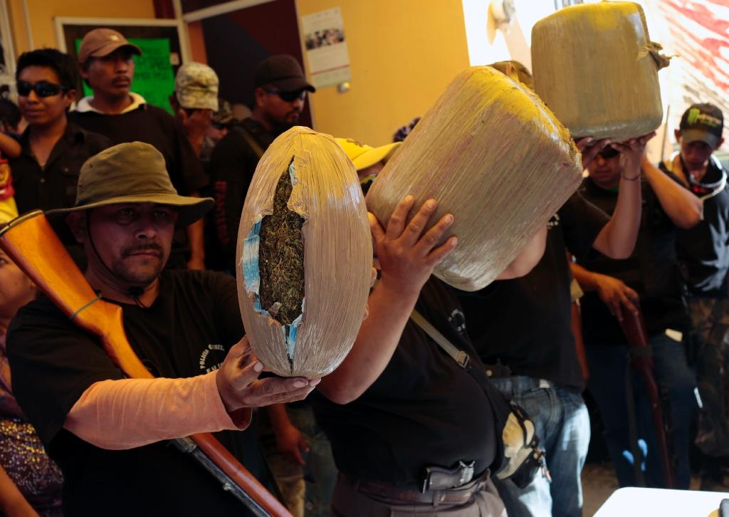 Members of a vigilante group show weapons and marijuana allegedly seized during an operation to apprehend suspected offenders, in Chilpancingo, Guerrero State, Mexico, on February 1, 2015 (AFP Photo/Pedro Pardo)