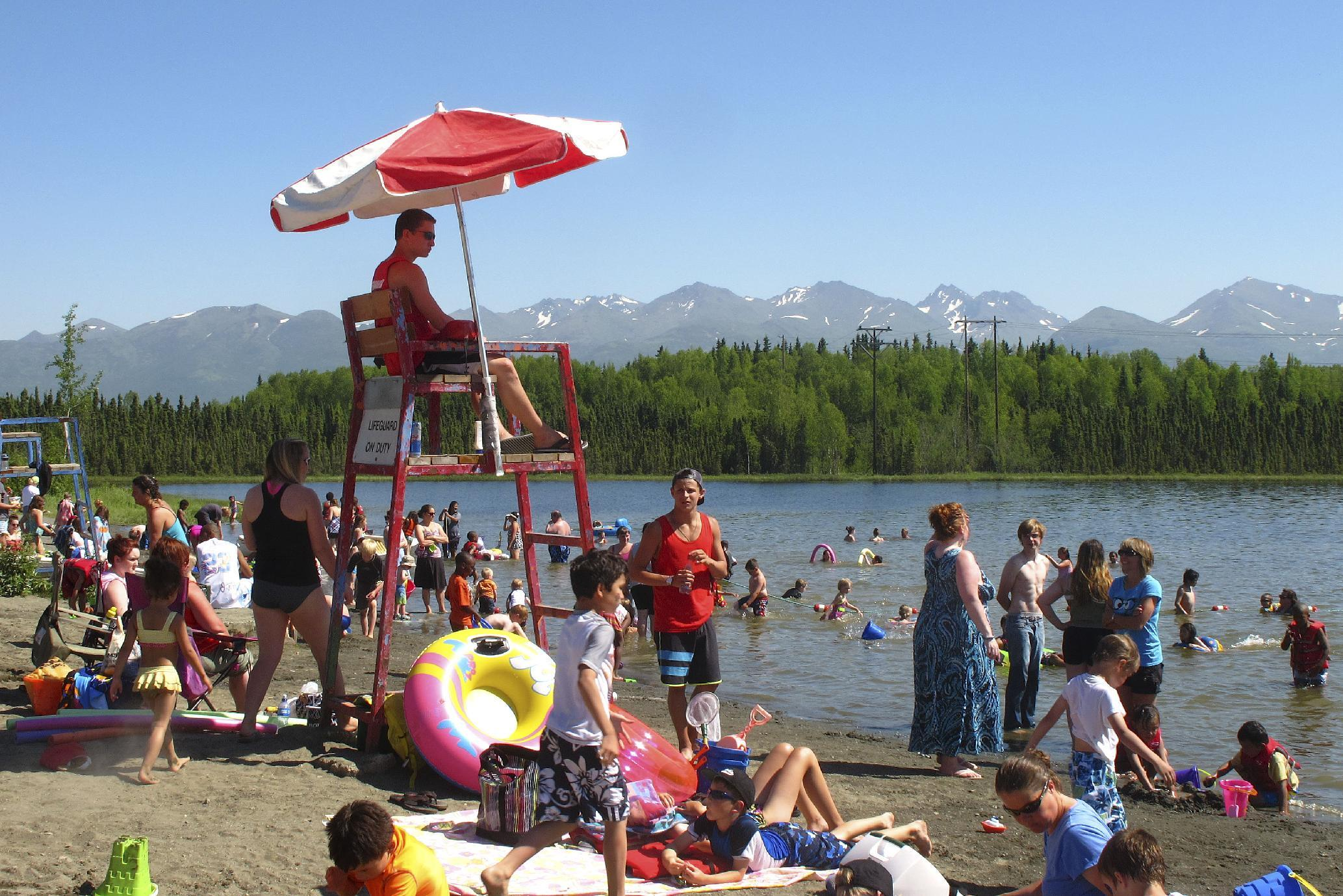 FILE - People swim and sunbathe at Goose Lake in Anchorage, Alaska on Monday, June 17, 2013. Alaska's largest city and other parts of the state are experiencing a long stretch of higher than normal temperatures. The jet stream, the river of air high above Earth that generally dictates the weather, usually rushes rapidly from west to east in a mostly straight direction. But lately it seems to be wobbling and weaving like a drunk driver, wreaking havoc as it goes. The most recent example is mid-June where some towns in Alaska hit record highs. (AP Photo/Rachel D'Oro)
