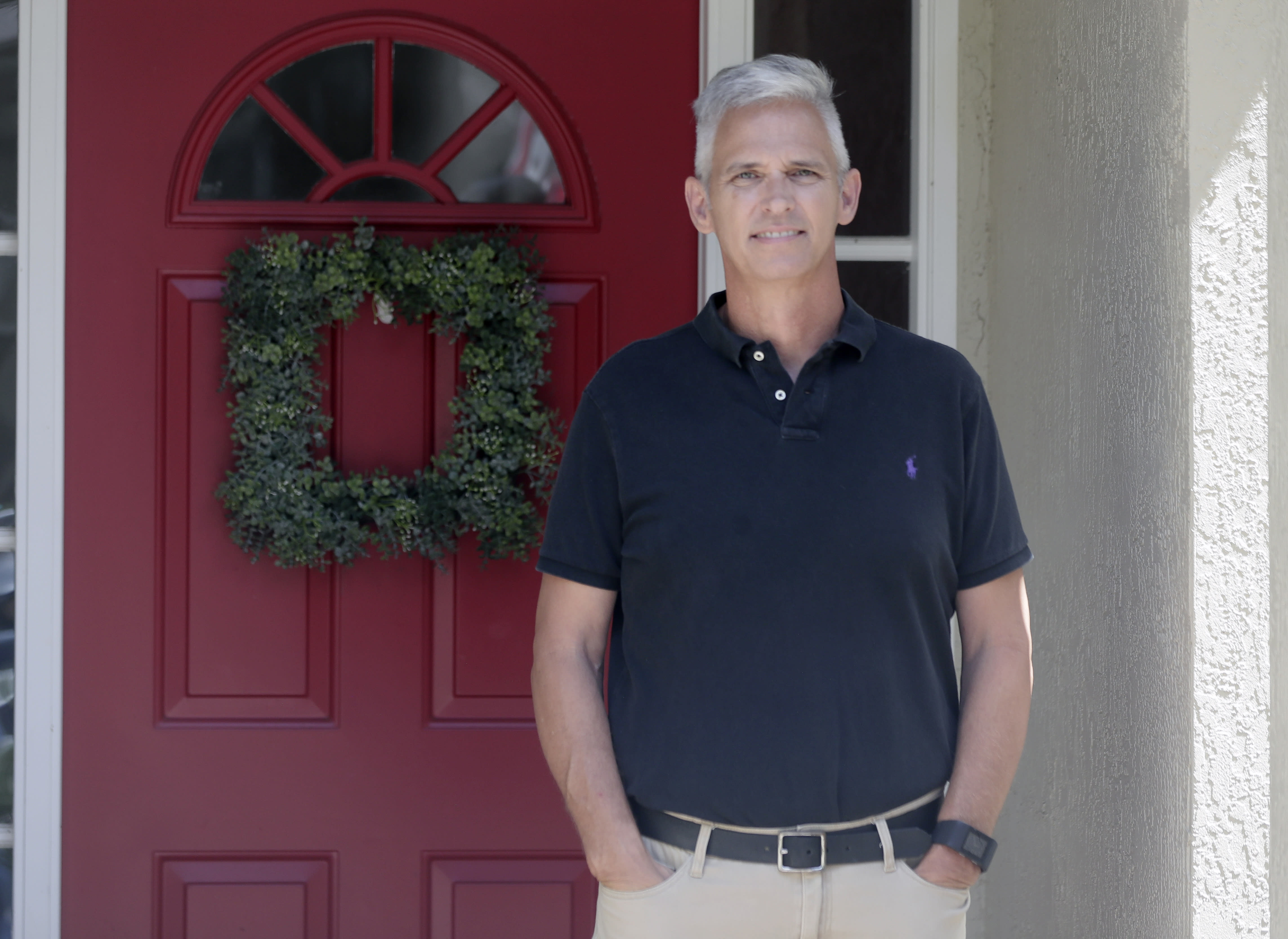 Bob Garick stands by the entrance to his home Wednesday, Aug. 5, 2020, in Oviedo, Fla. Garick was looking forward to being a field supervisor during the door-knocking phase of the 2020 census, but as the number of new coronavirus cases in Florida shot up last month, he changed his mind and decided not to take the job. The loss of these so-called door-knockers - formally known as enumerators - is happening just when the agency faces newly tightened deadlines to reach the hardest to count communities, including minorities and immigrants. (AP Photo/John Raoux)