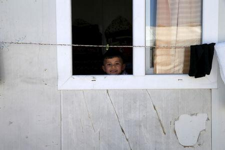 Yazidi boy Emad, 5, looks out of his family's home at a refugee camp near the northern Iraqi city of Duhok April 19, 2016. REUTERS/Ahmed Jadallah