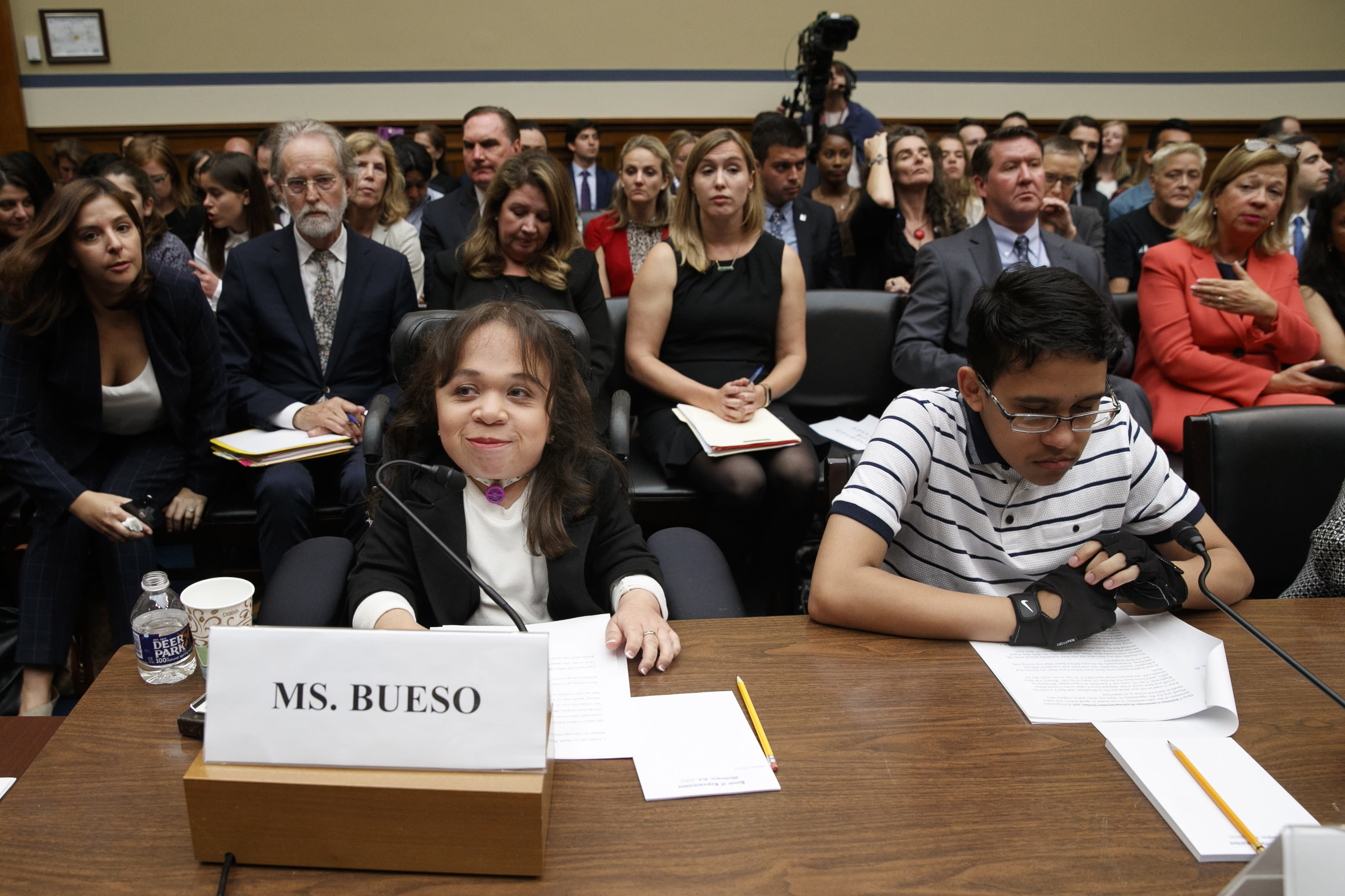 Maria Isabel Bueso, 24, of Concord, Calif., left, and Jonathan Sanchez, 16, of Boston, who both have medical deferred action, take their places at the start of a House Oversight subcommittee hearing into the Trump administration's decision to stop considering requests from immigrants seeking to remain in the country for medical treatment and other hardships, Wednesday, Sept. 11, 2019, on Capitol Hill in Washington. (AP Photo/Jacquelyn Martin)